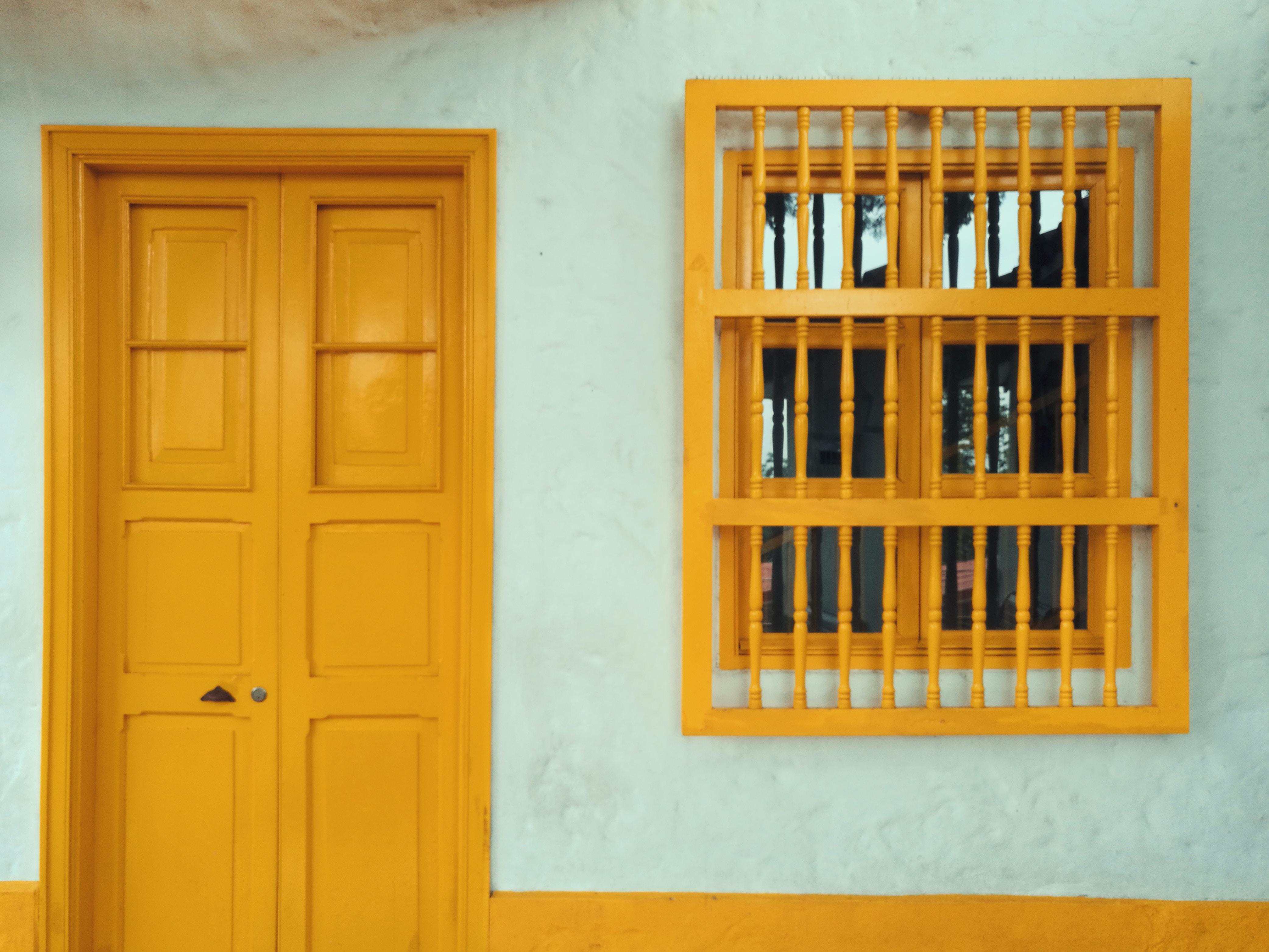 yellow 8-panel door beside window