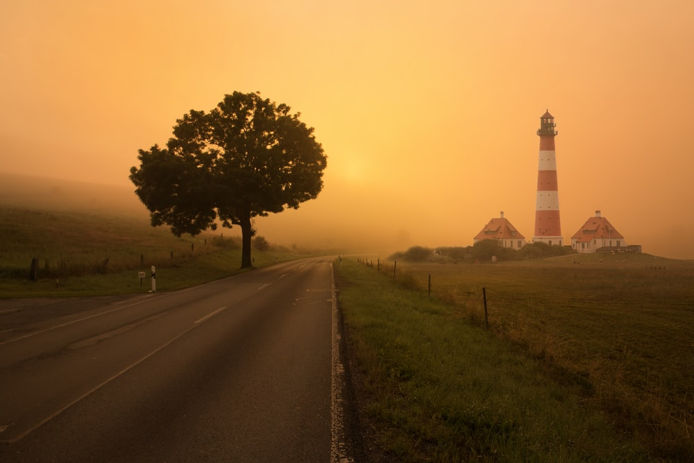 empty roadway with lighthouse and two houses