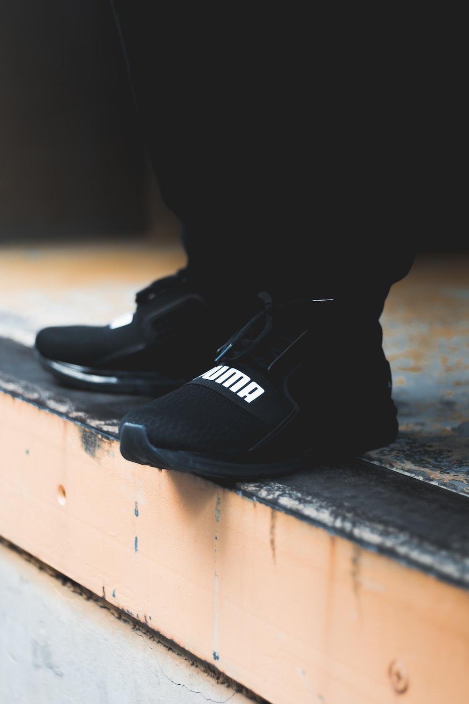 person wearing black Puma low-top sneakers standing on sidewalk
