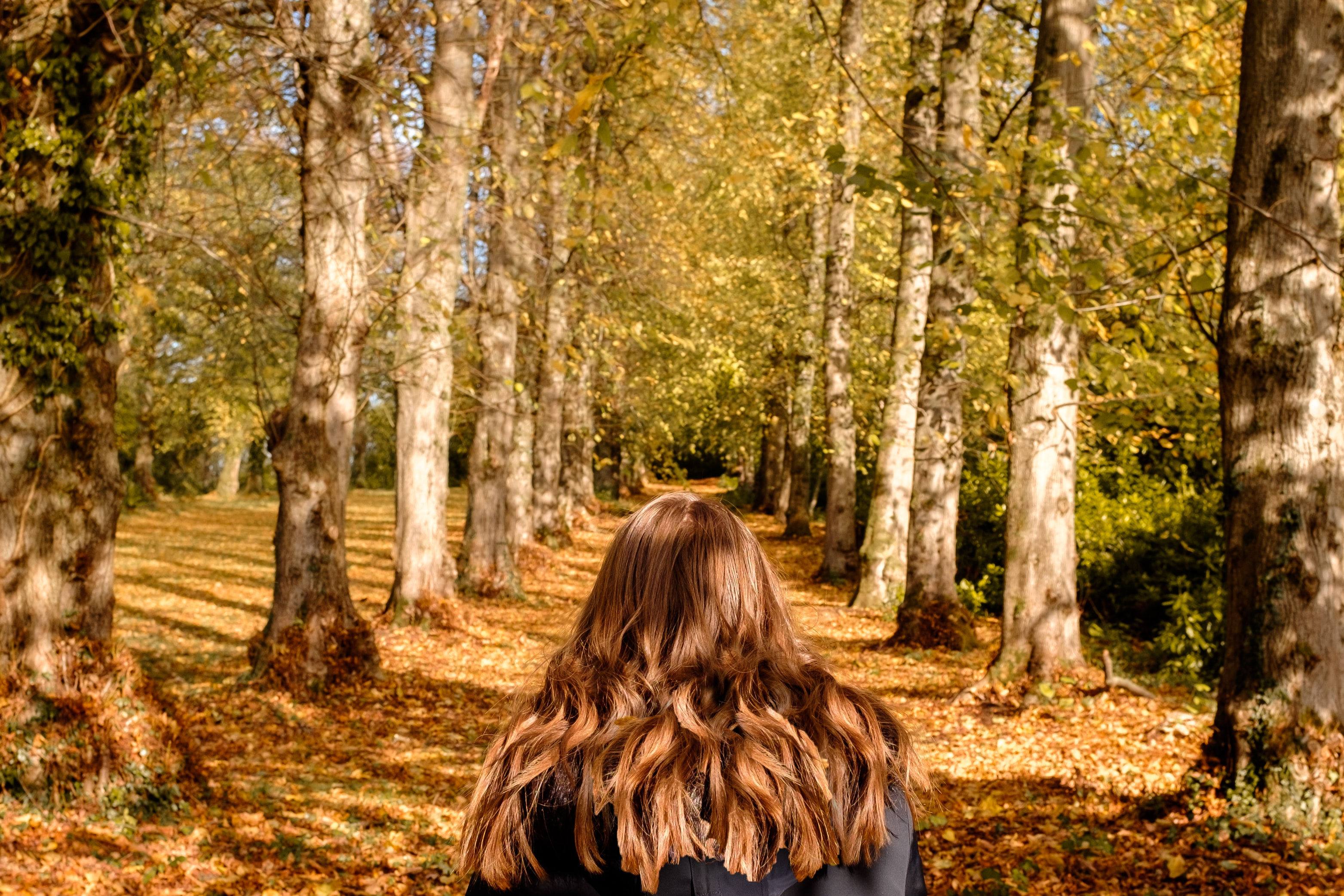 woman walking in the middle of pathway with trees