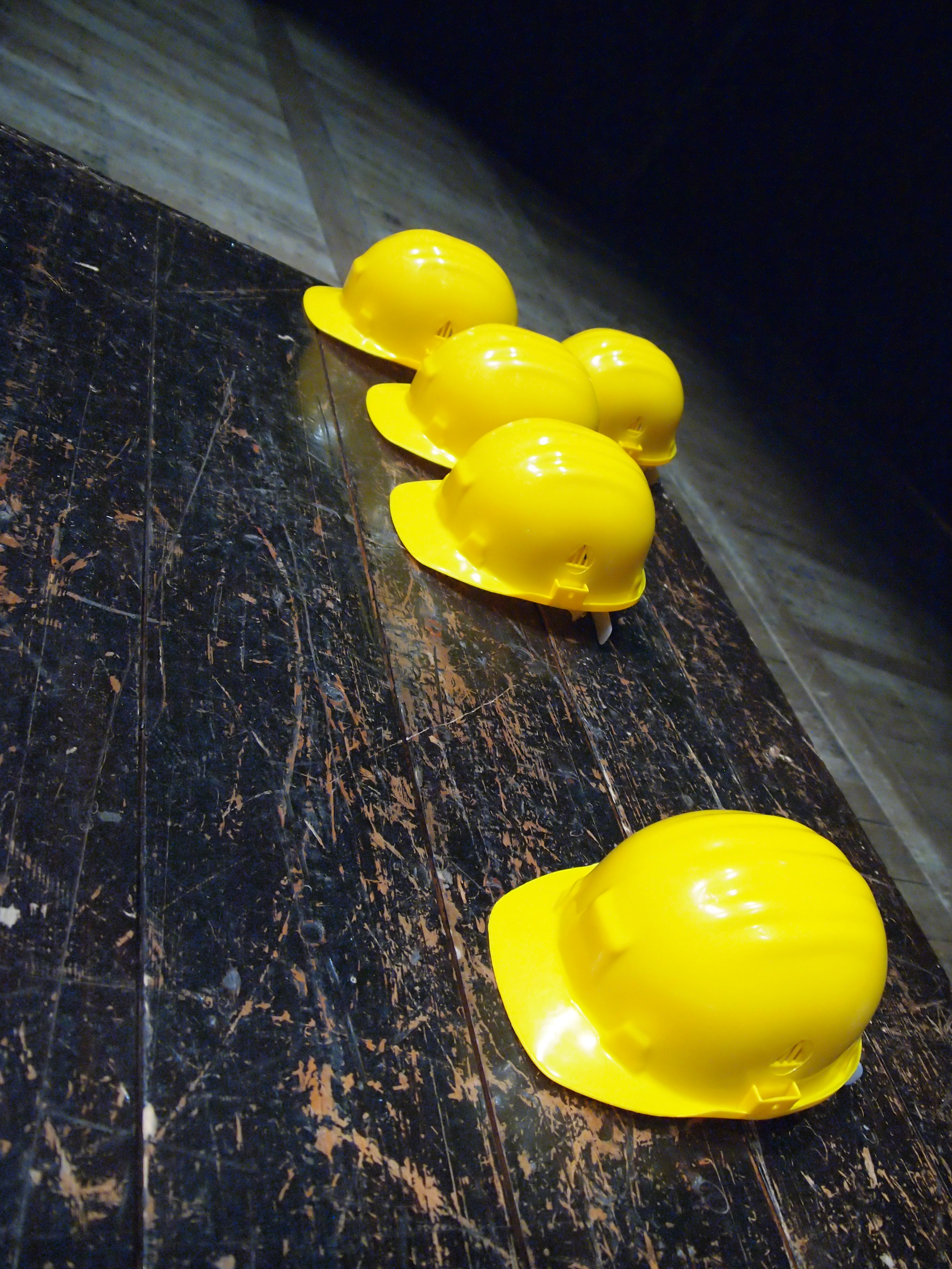 five yellow hard hats on gray surface