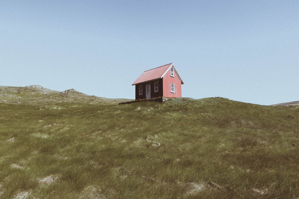 red wooden cabin on hill under blue sky at daytime