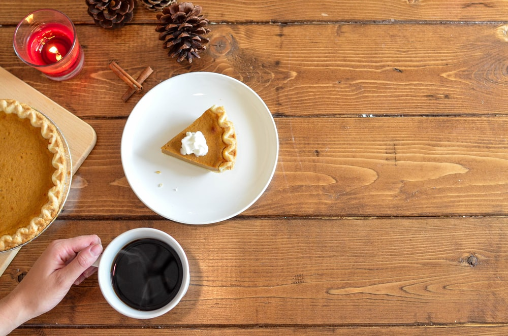 slice of pie with whipped cream on ceramic plate near coffee