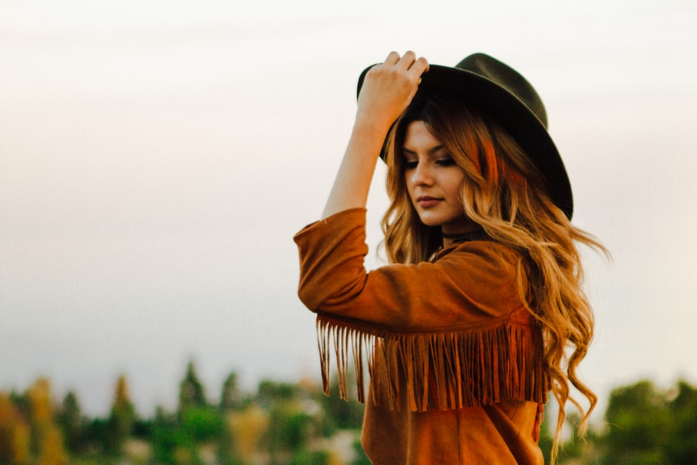 woman wearing brown jacket with fringe holding hat during daytime