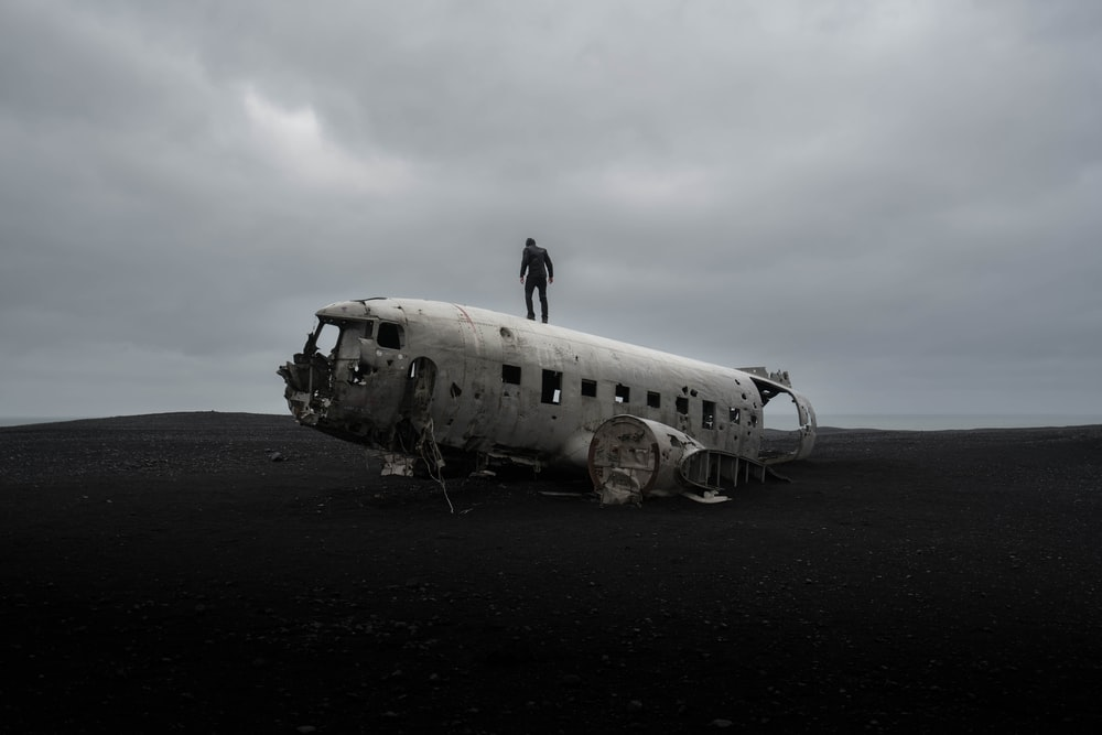 person standing on wrecked airplane under gloomy sky