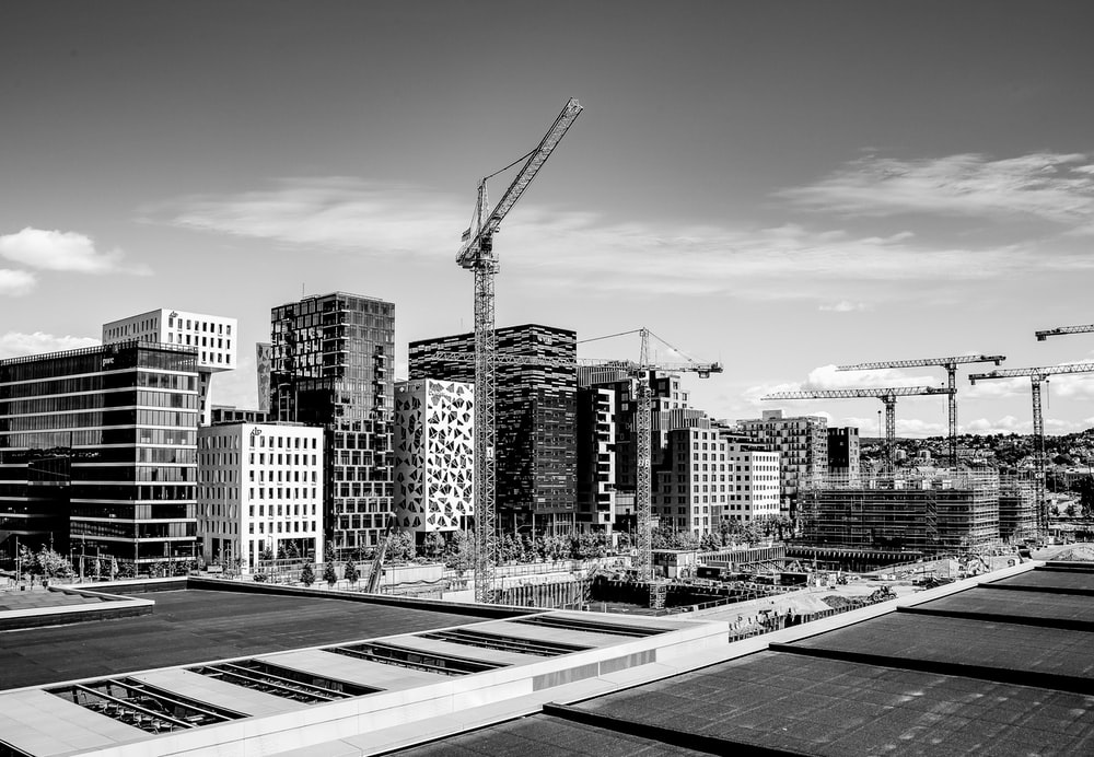 grayscale photography of tower crane on street near buildings