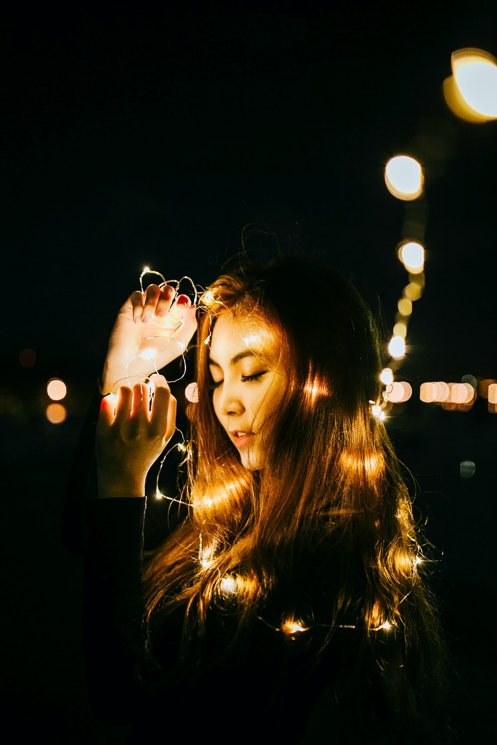 bokeh photography of woman holding string lights