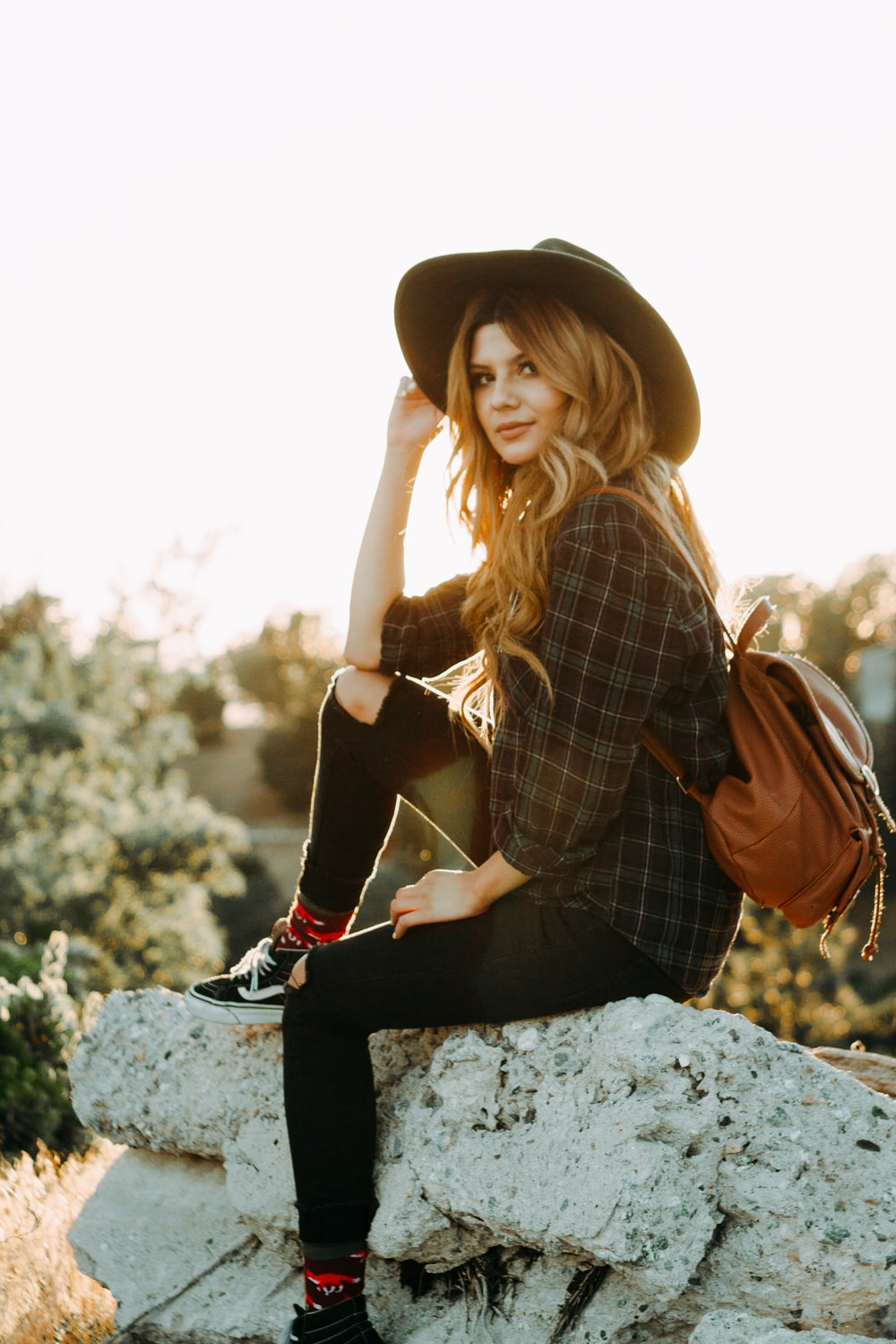 golden hour photography of woman sitting on rock while holding her hat