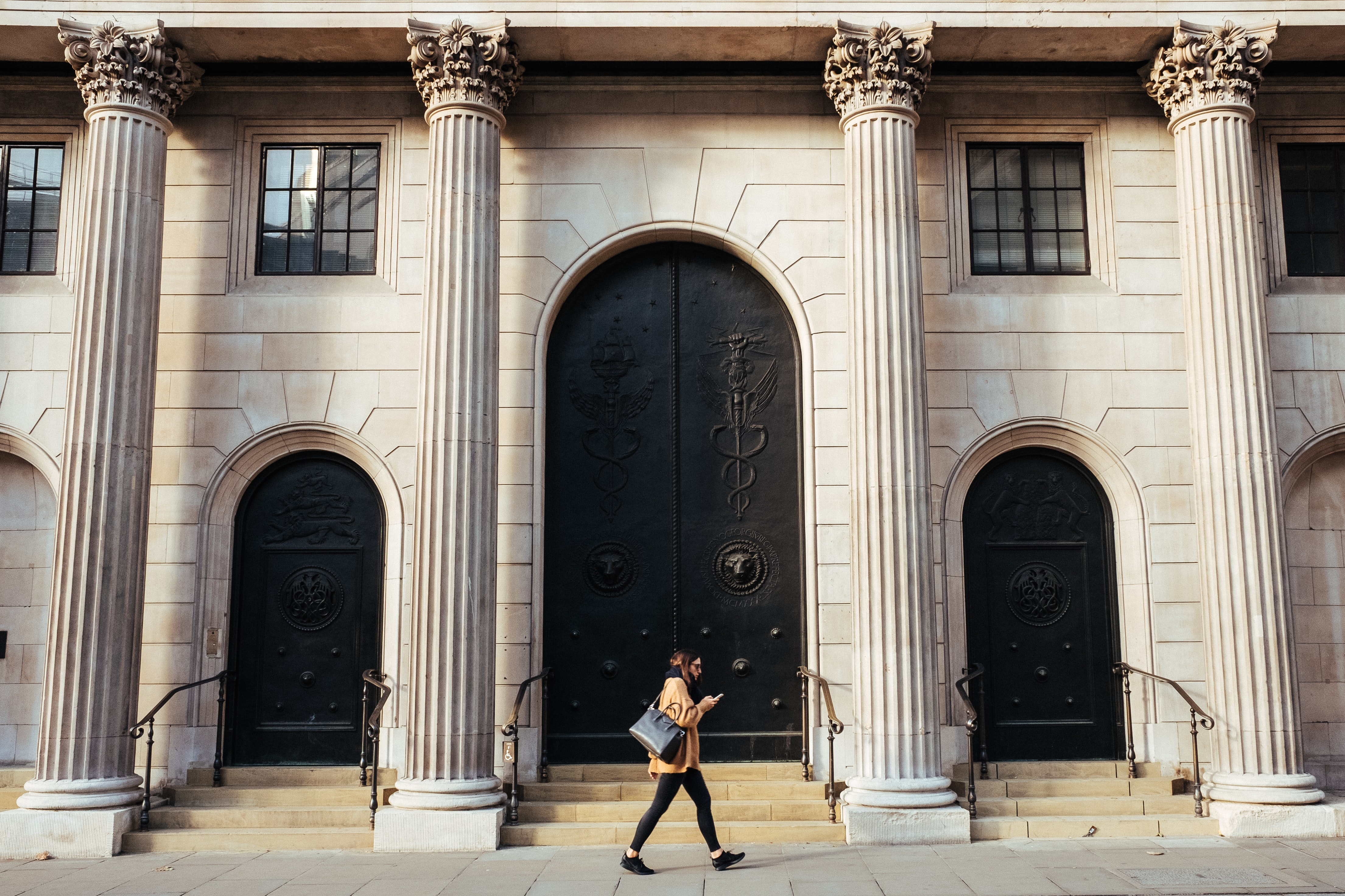 woman walking in-front of white building with ionic pillars