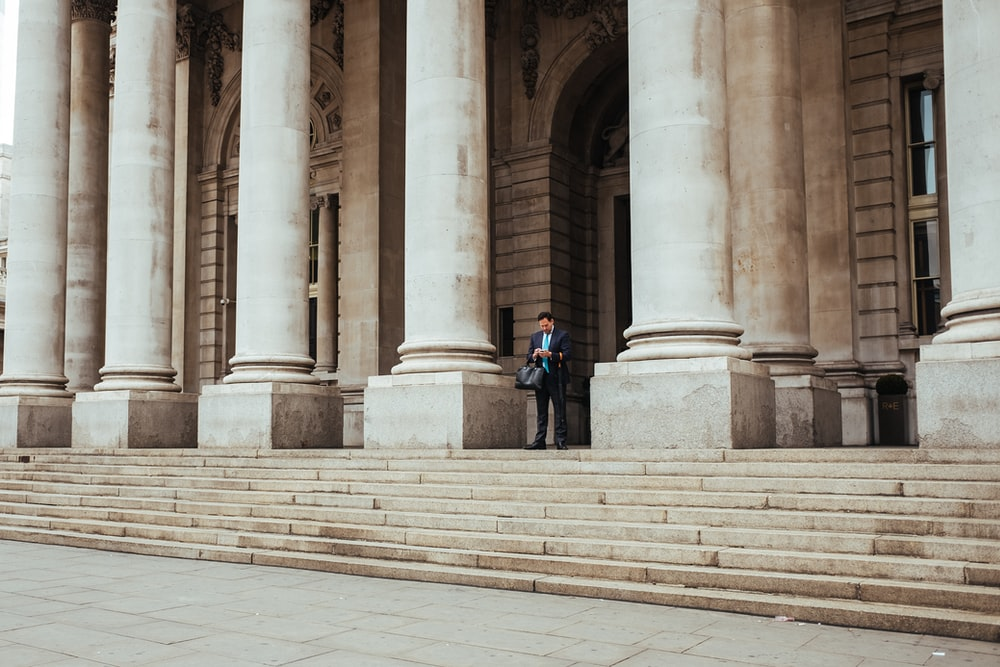 man standing in the middle of pillar building