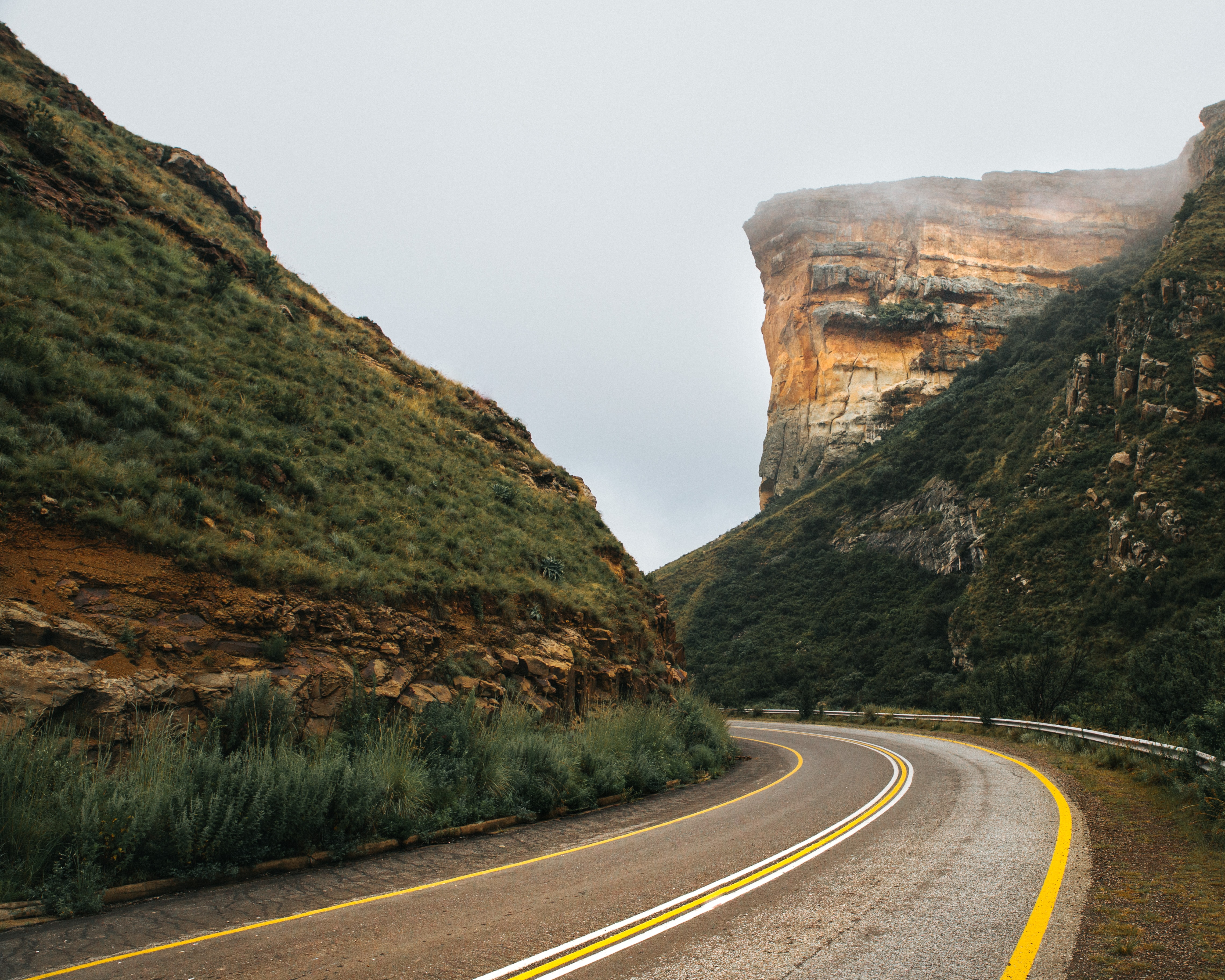 gray paved highway in between of mountain