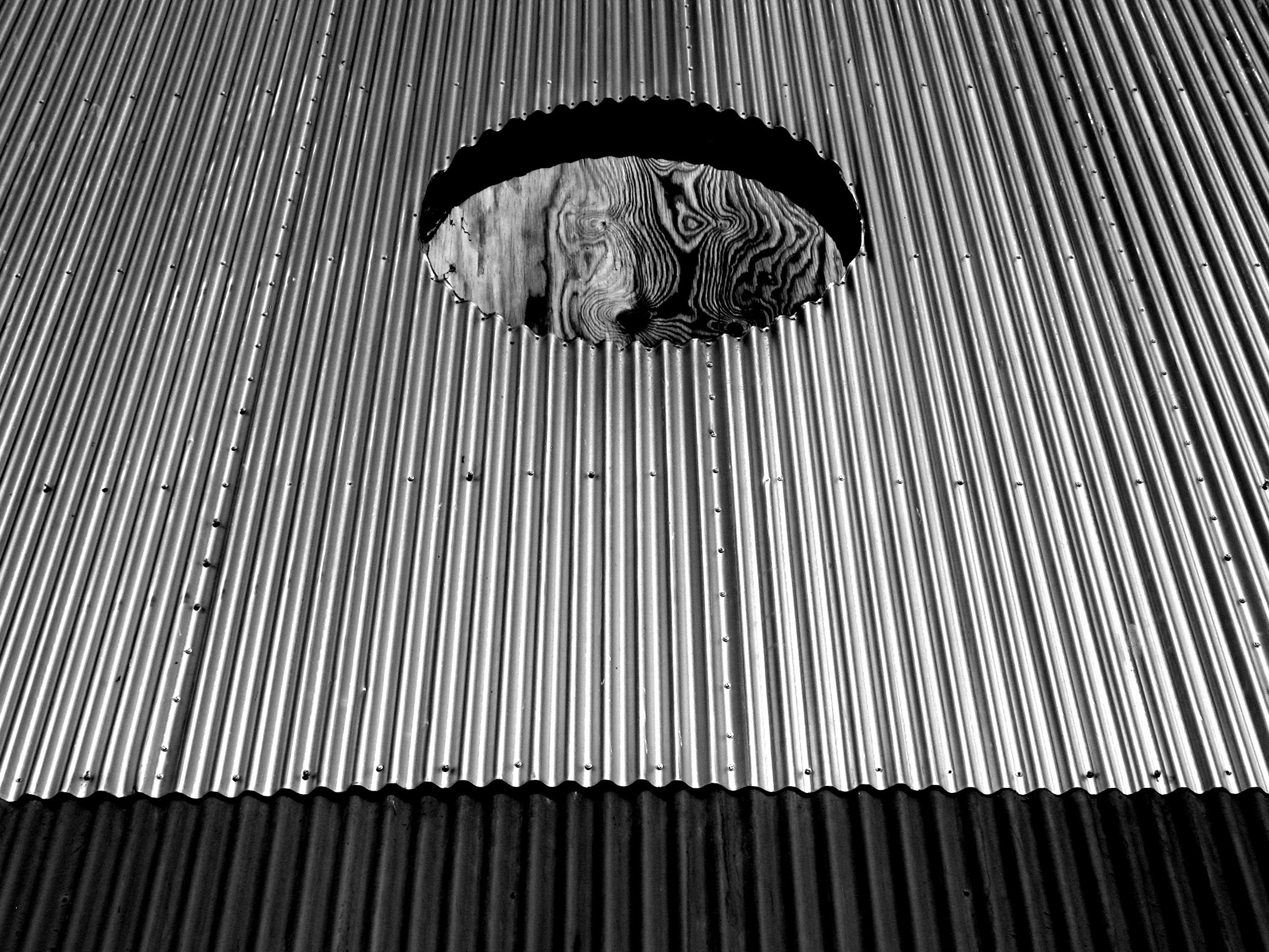 aerial photography of gray corrugated roof with hole
