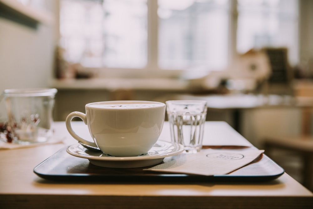 white ceramic tea cup on white ceramic saucer inside room with glass windows