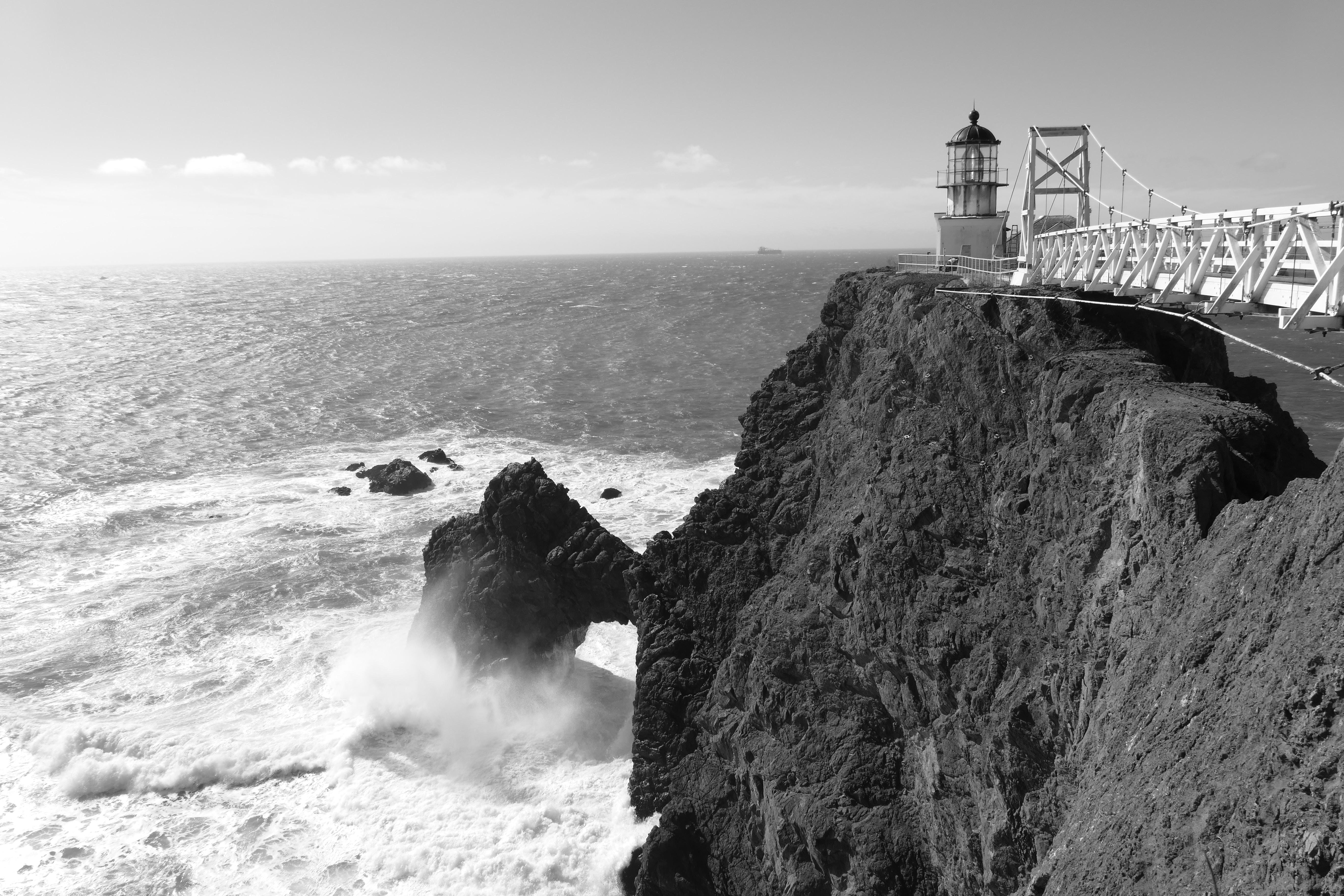 greyscale photography of lighthouse near bridge