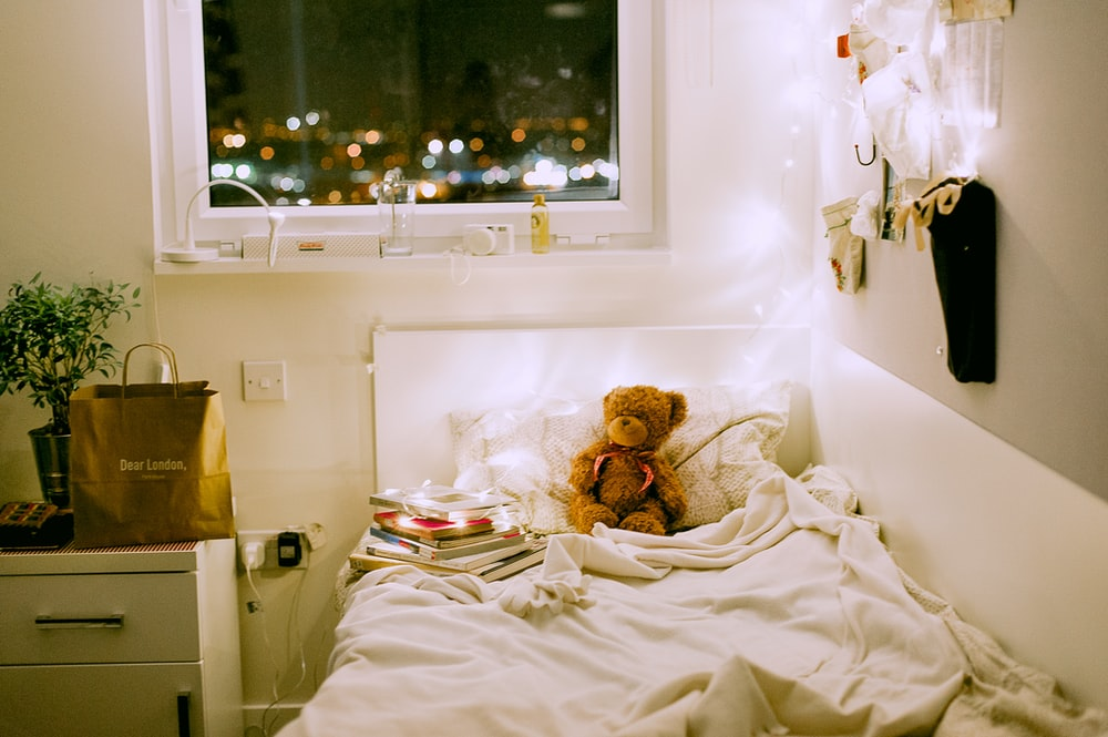 teddybear on bed near night stand and window