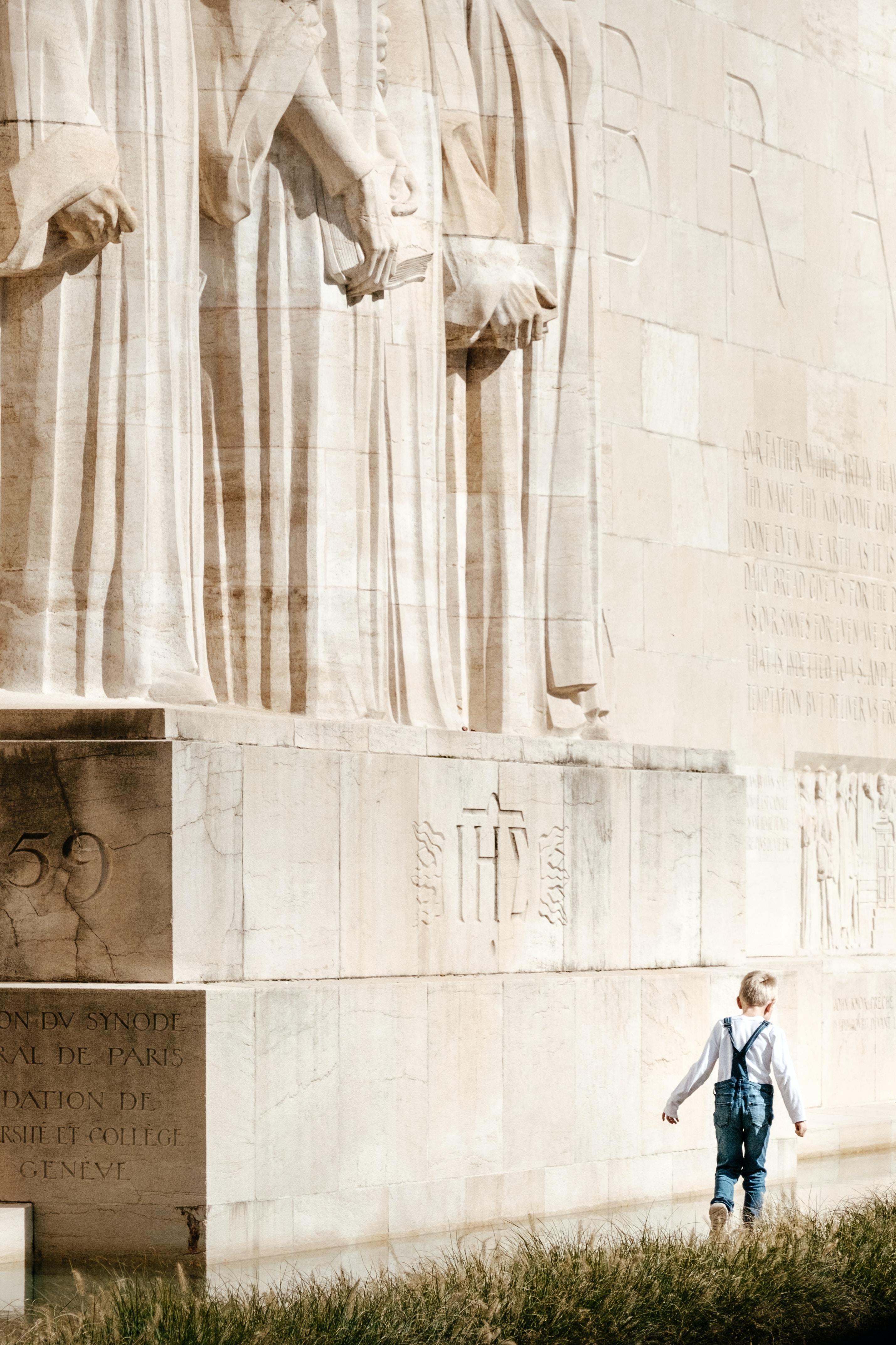 boy walking beside the statue