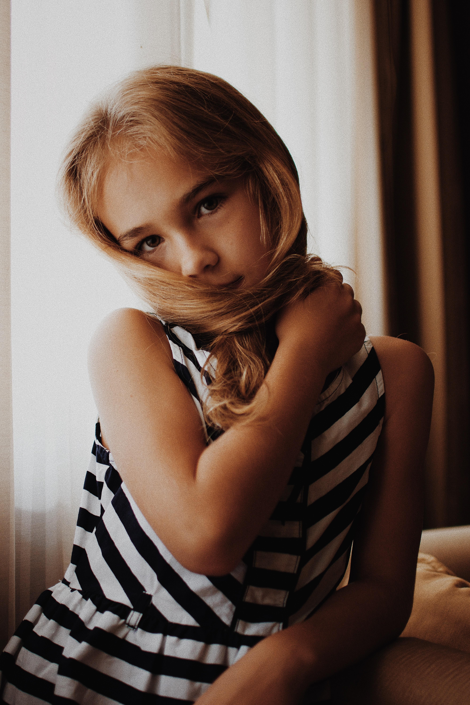 girl's holding her hair beside window