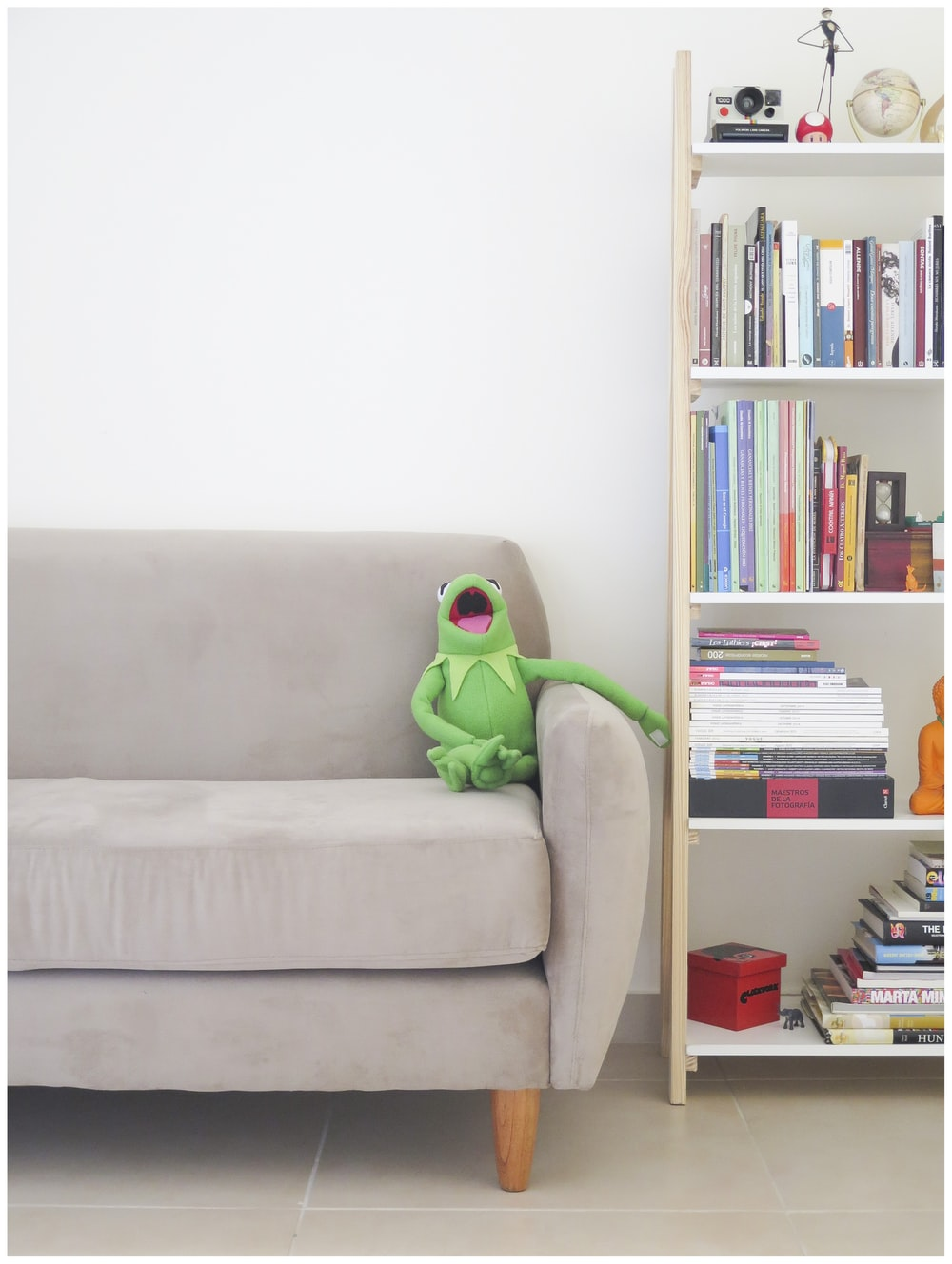 The Muppets Kermit plush toy on gray sofa