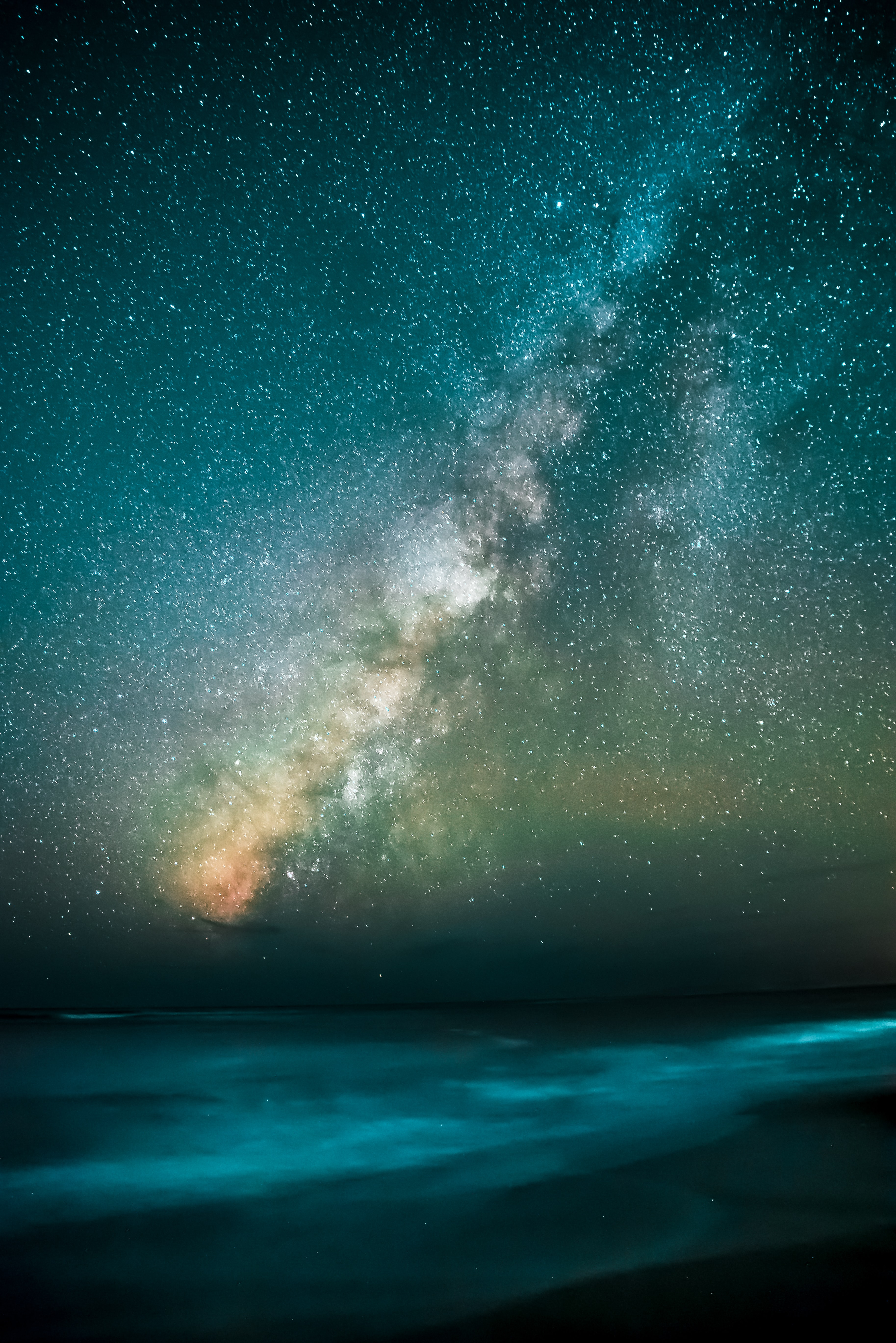 Milky way stars over the waves on the beach