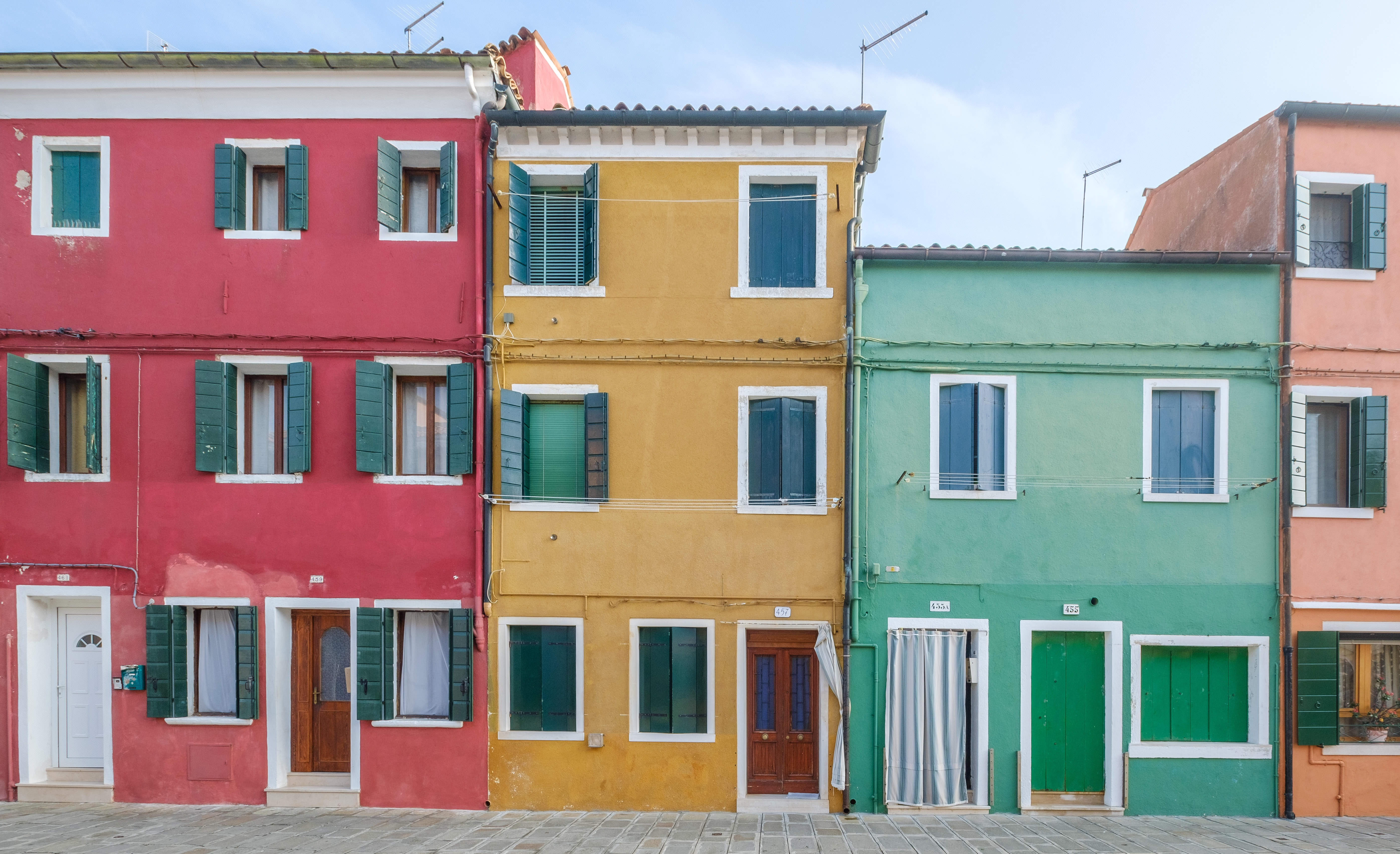 three assorted-color concrete houses under blue and white sky at daytime