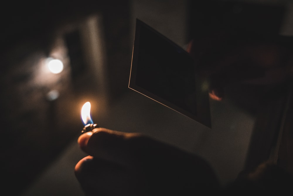 shallow focus photography of person holding a lighter