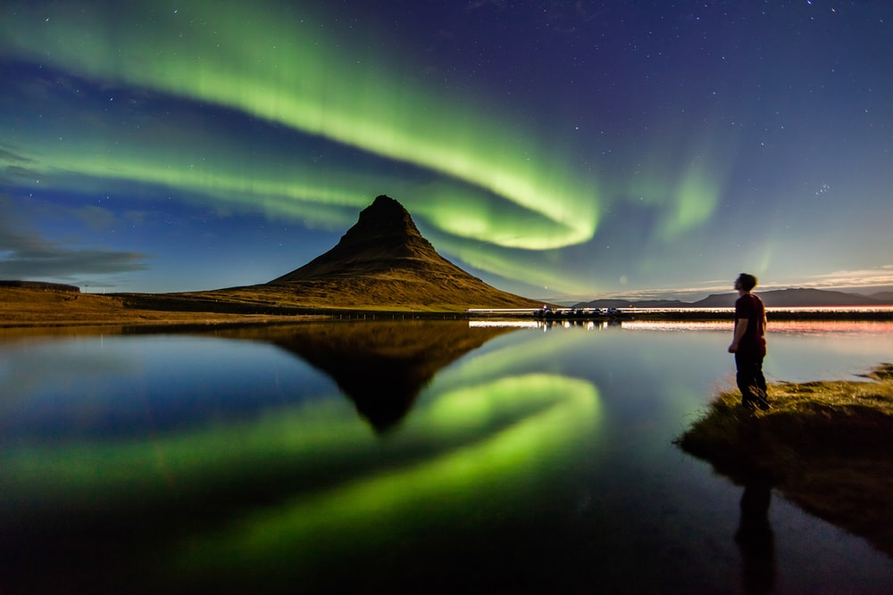man standing beside the body of water with Aurora lights in the sky