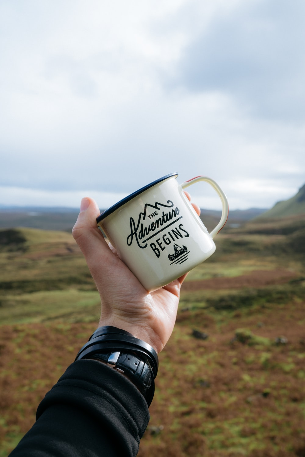person holding beige and black The Adventure Begins-printed mug during daytime