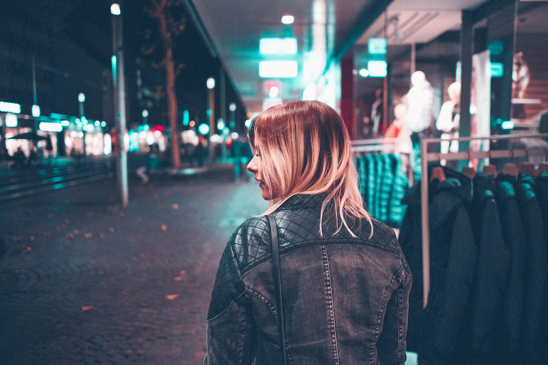woman in black jacket walking along the street