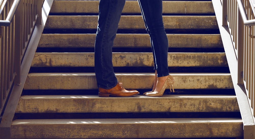 two person wearing blue jeans standing on gray concrete stair