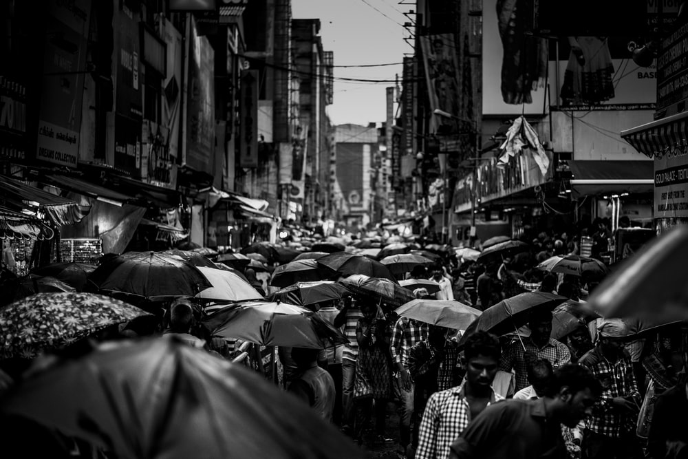grayscale photography of group of people holding umbrella