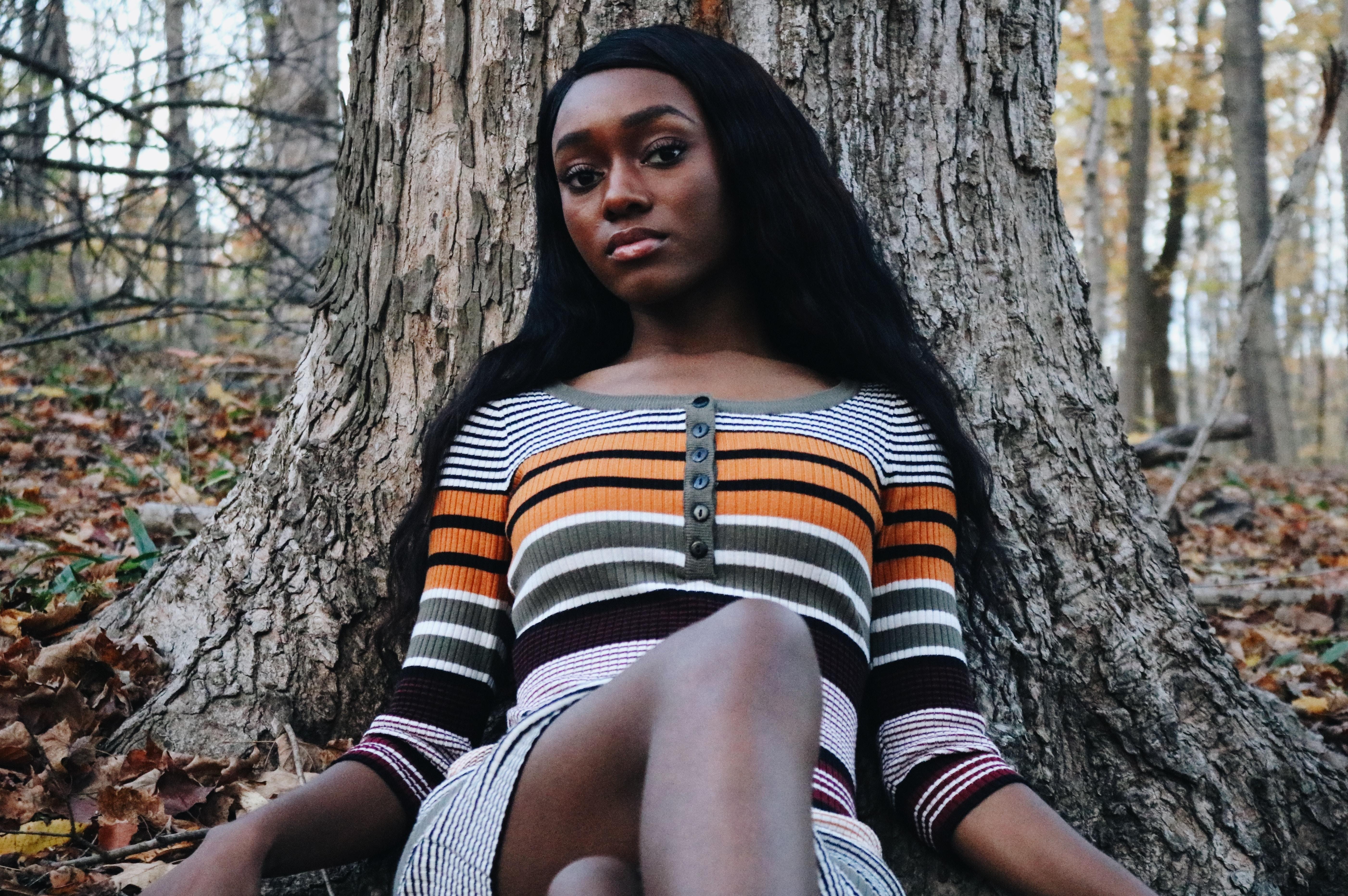 woman wearing striped shirt laying near tree