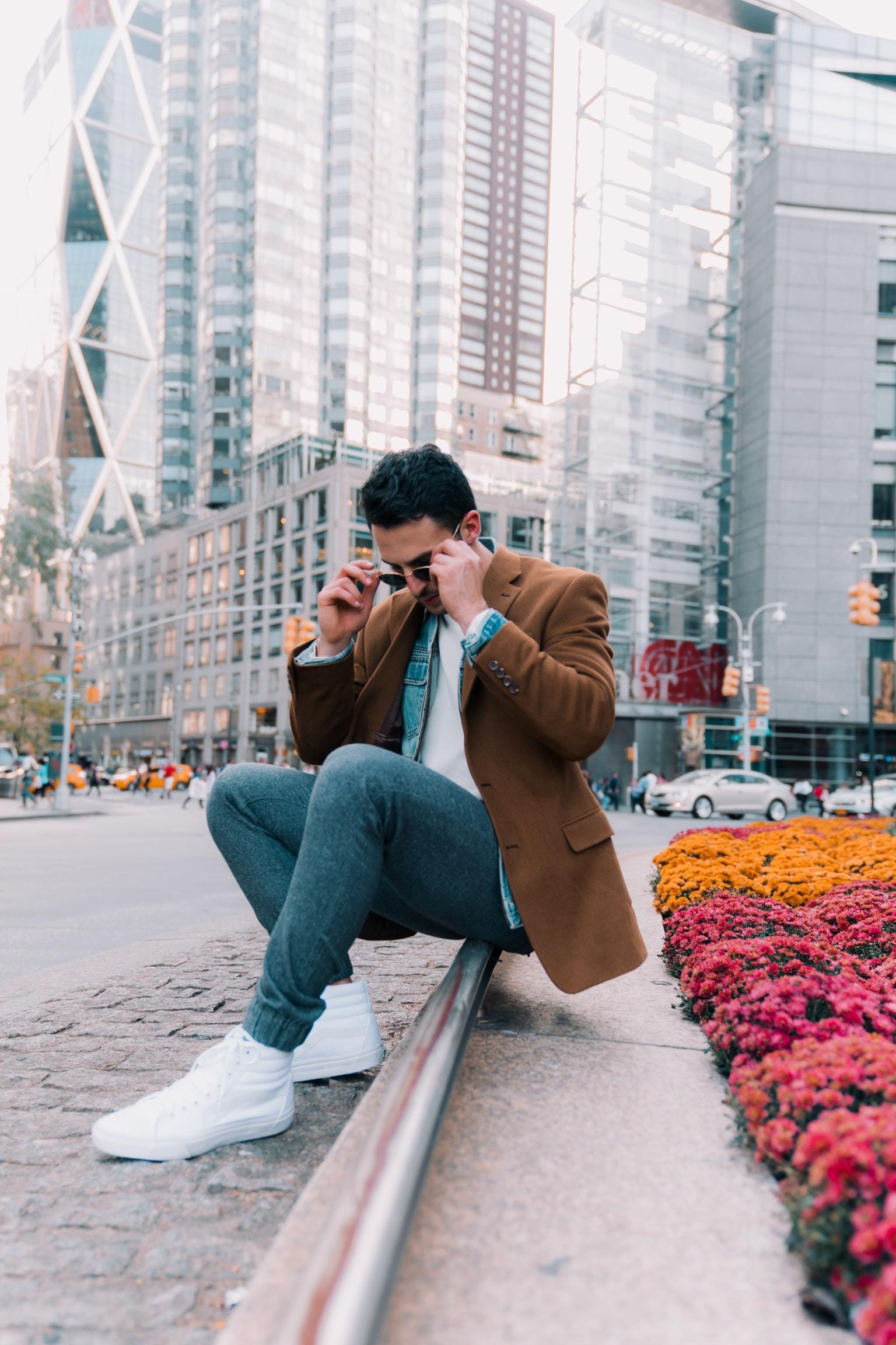 man sitting on sidewalk overlooking white skyscraper during daytime