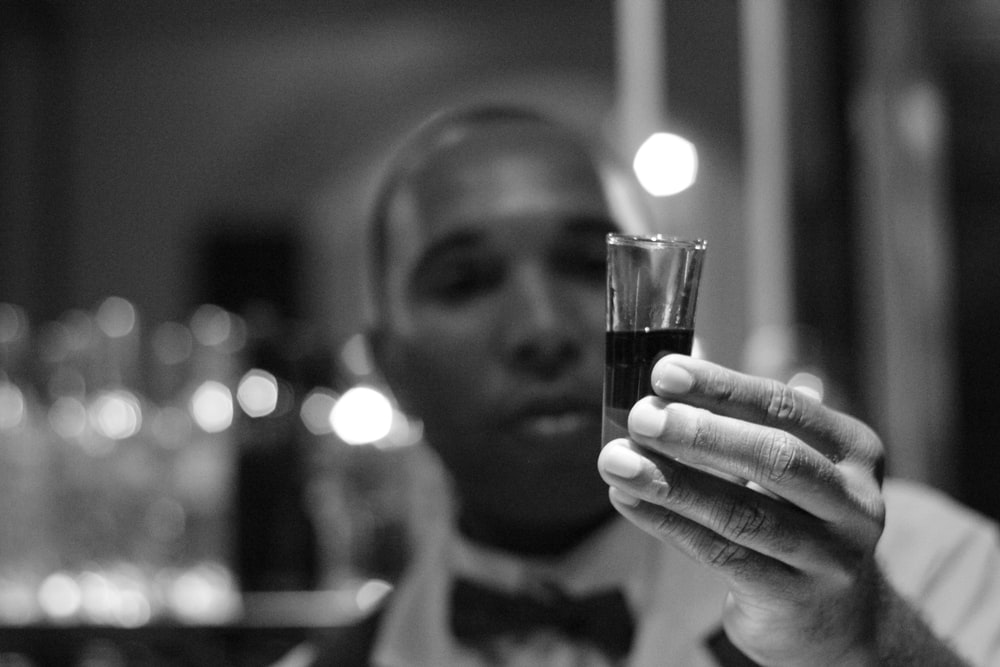 grayscale photo of man holding shot glass filled with liquid
