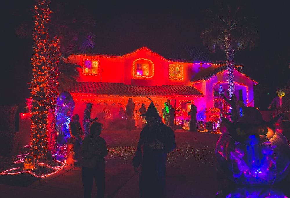 people standing near house with red light decor during night time