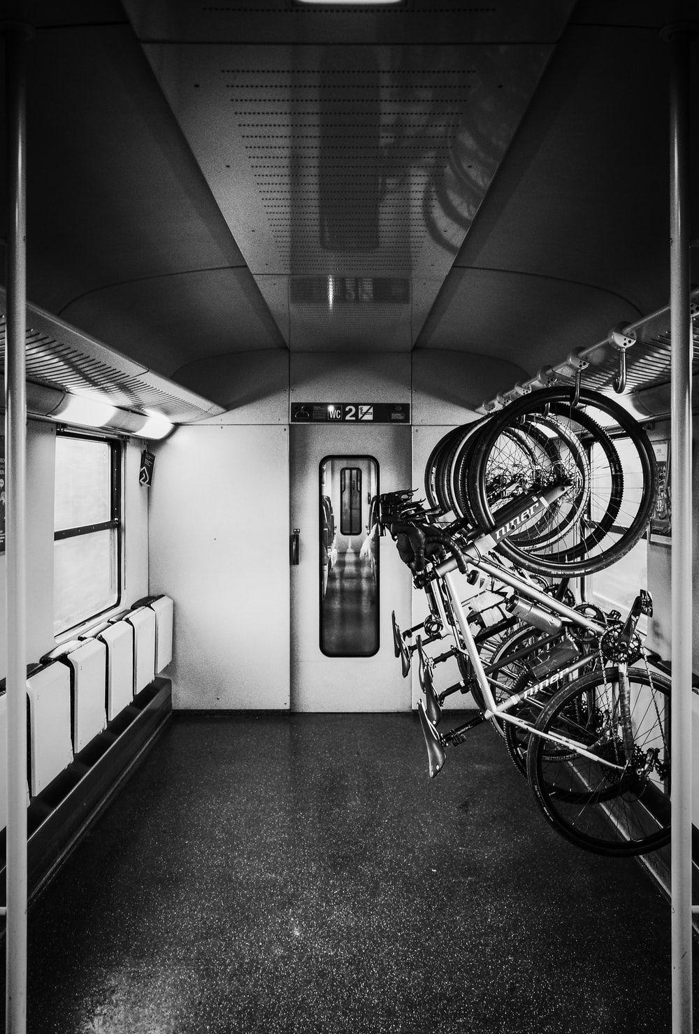 grayscale photo of bikes on rack