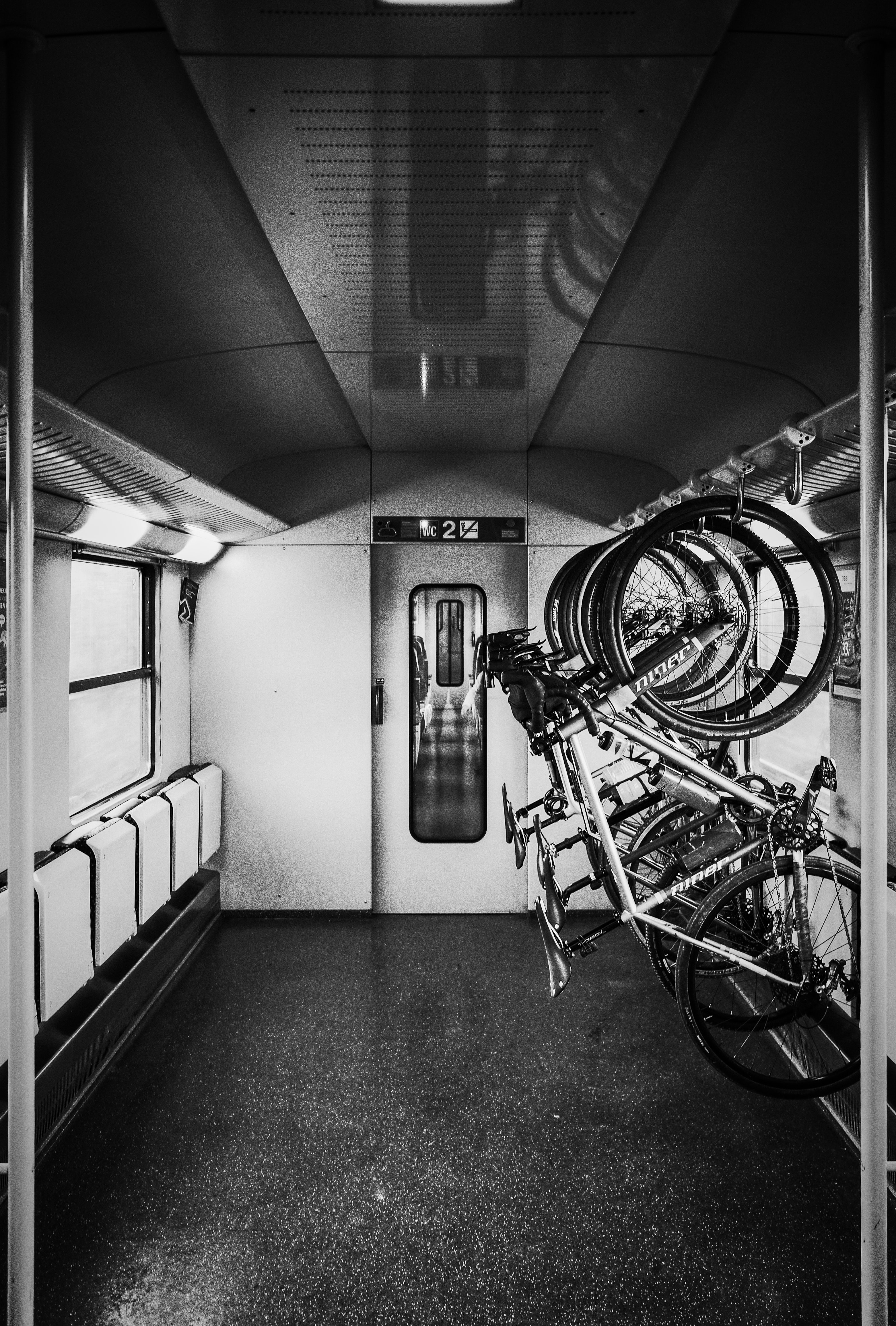 grayscale photo of bikes on rack