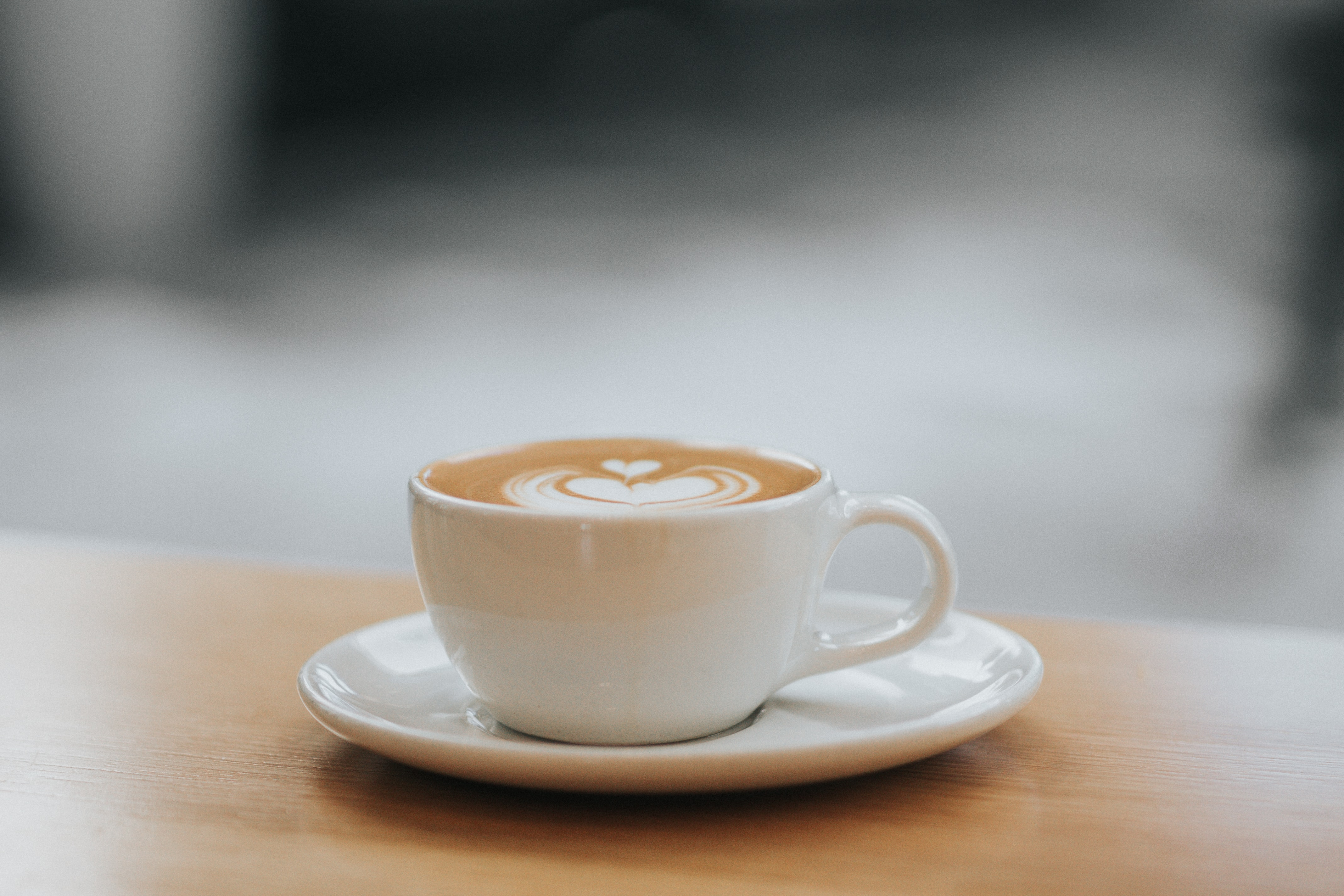 white ceramic teacup filled with coffee latte with saucer on the table photography