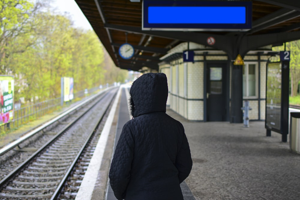 person in hoodie standing near train rail during daytime