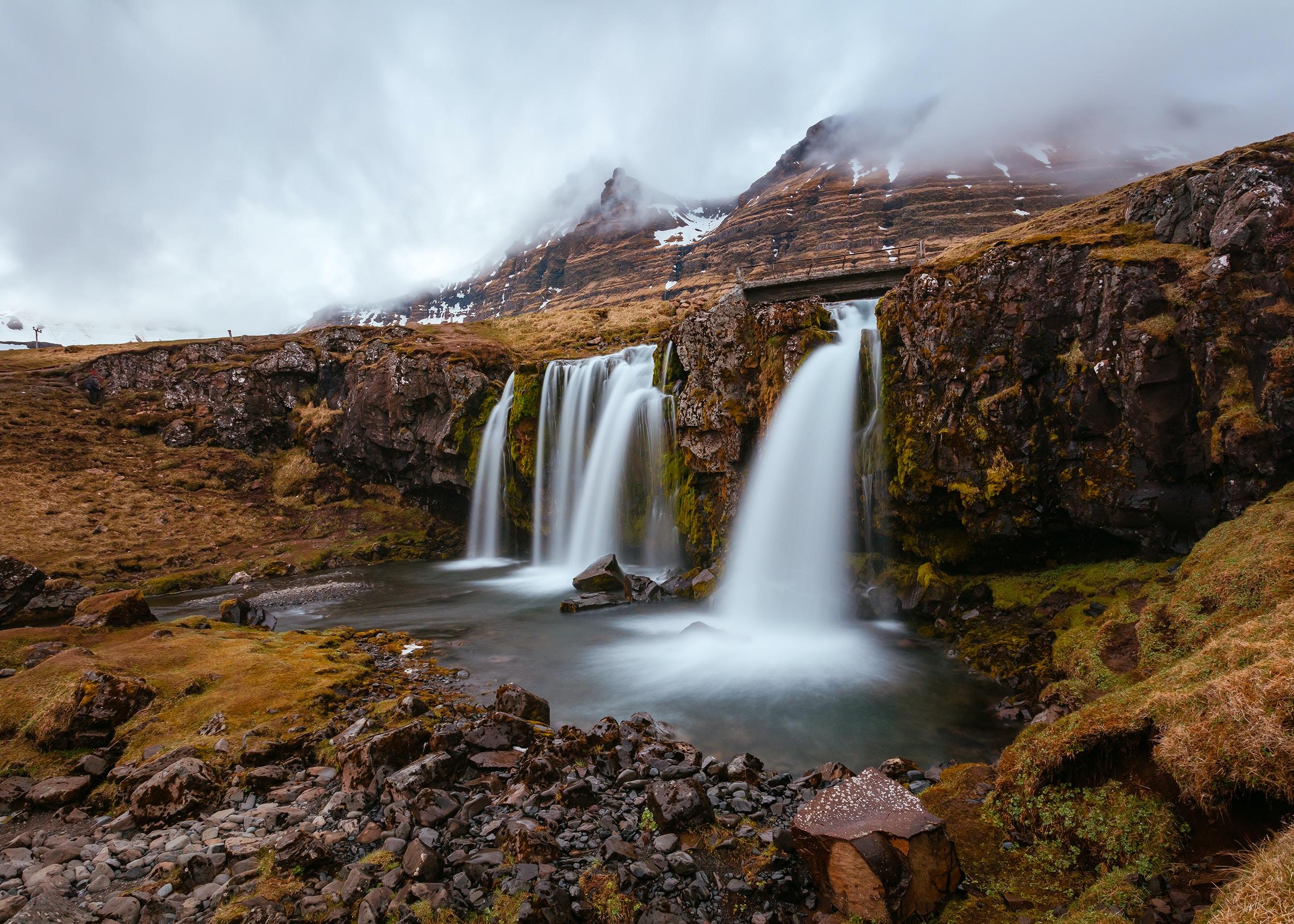waterfalls surround brown cliff during daytime