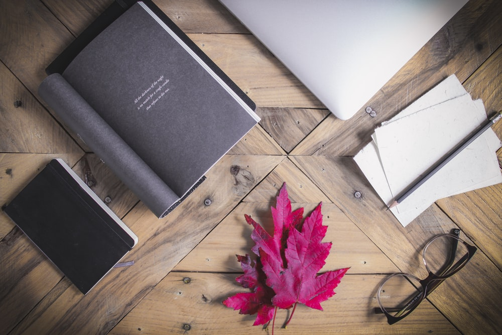 black book near pink maple leaf on brown wooden table