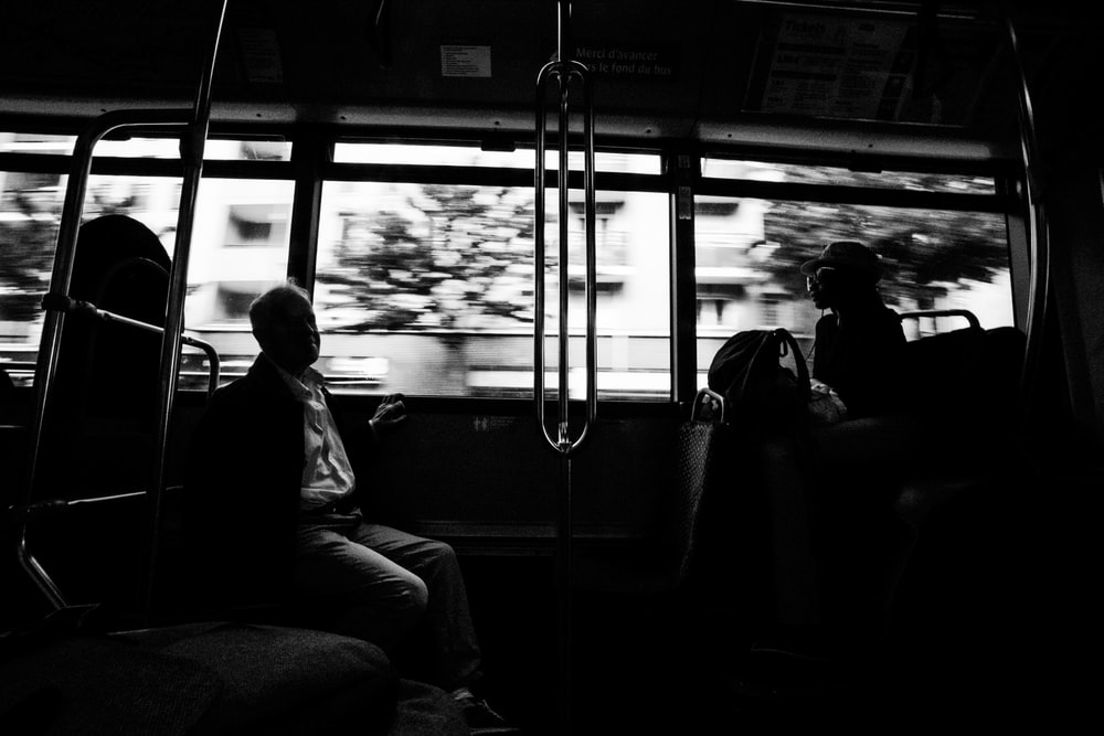 grayscale photo of several people on moving train