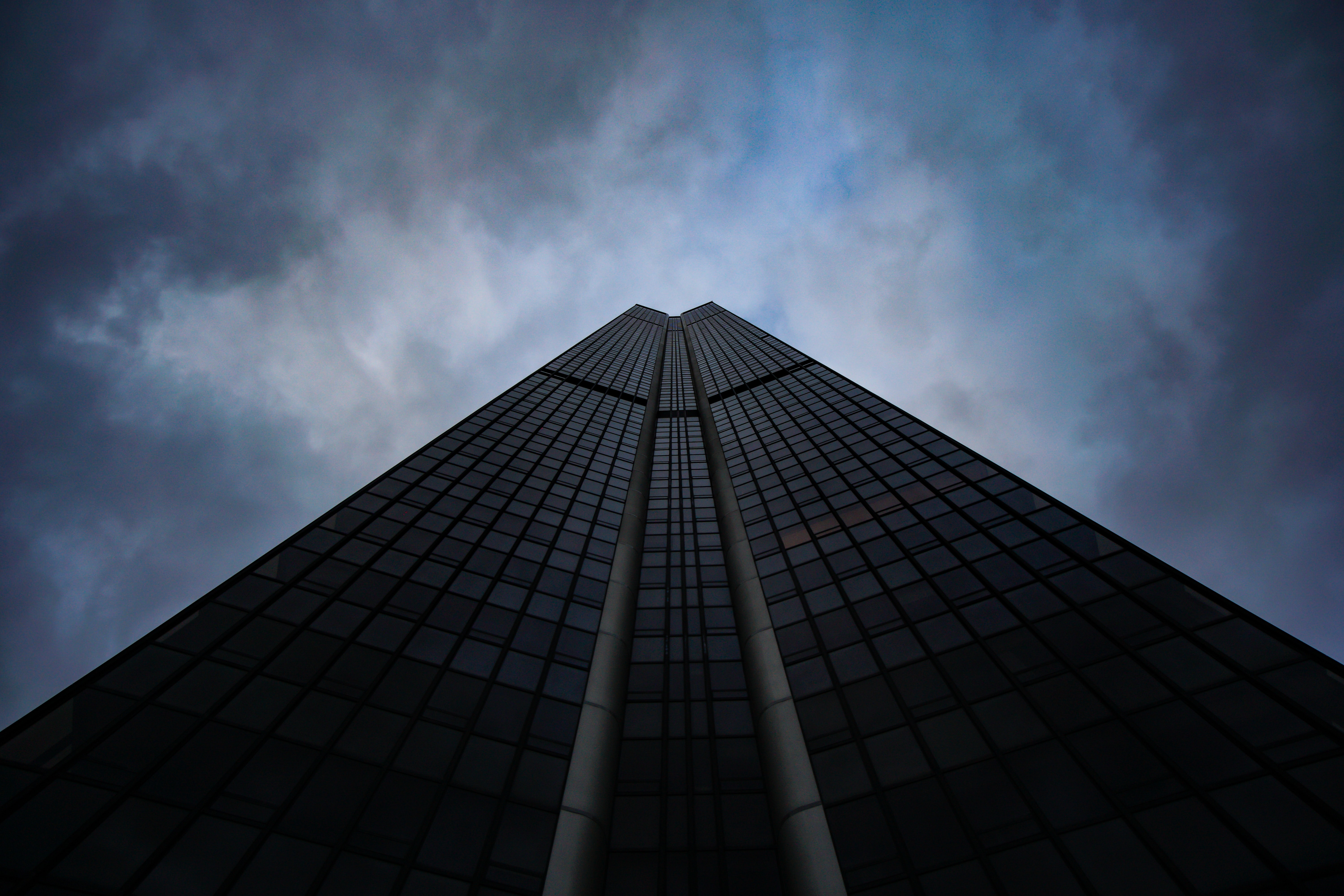 low-angle photography of black concrete building with glasses under cloudy sky