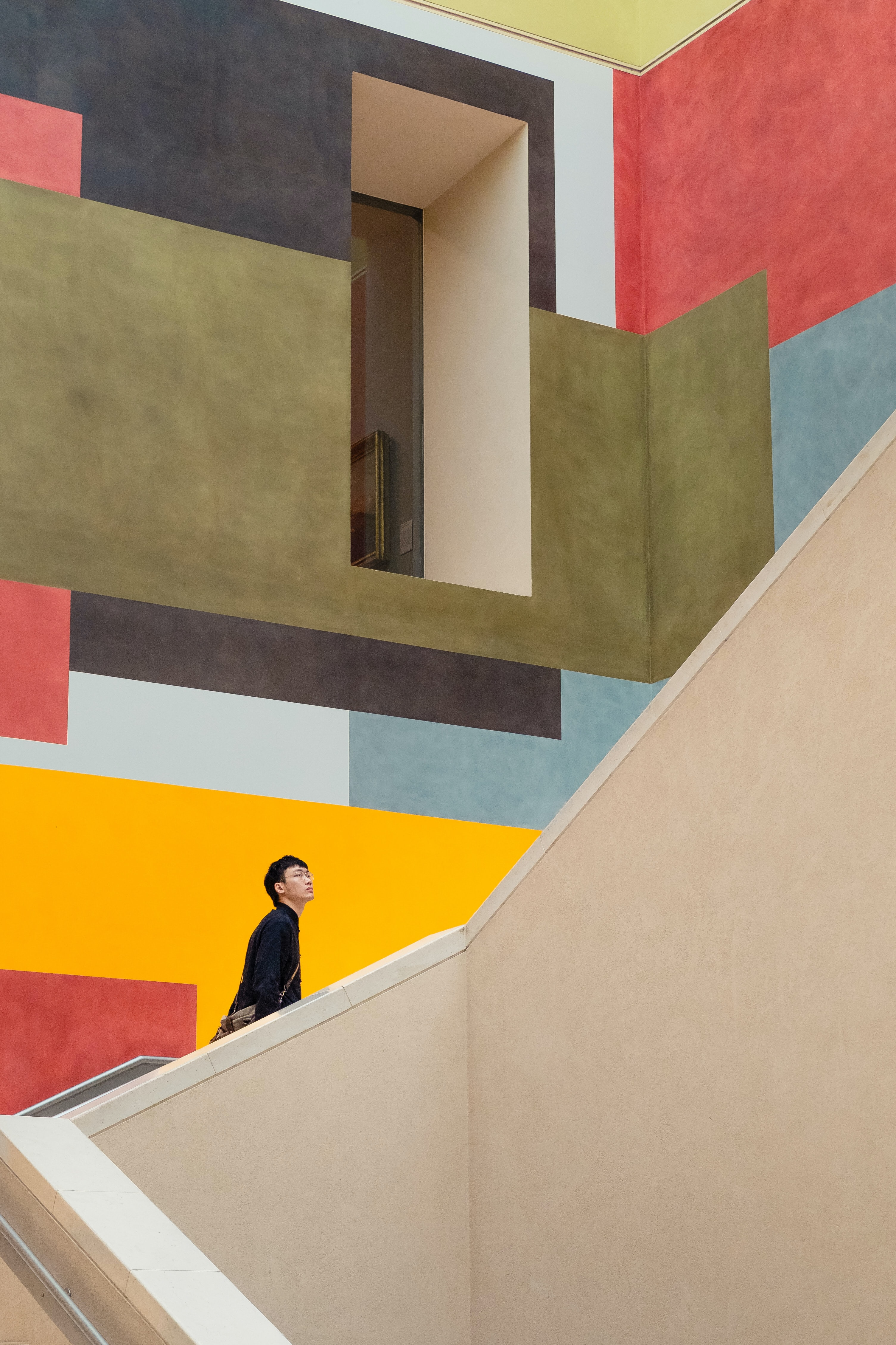 person walking on white spiral staircase looking at multicolored artistic wall