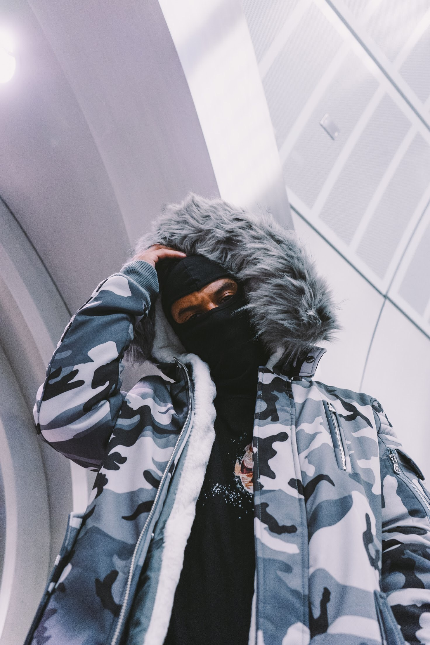 man wearing white, black, and blue camouflage fur-lined zip-up jacket