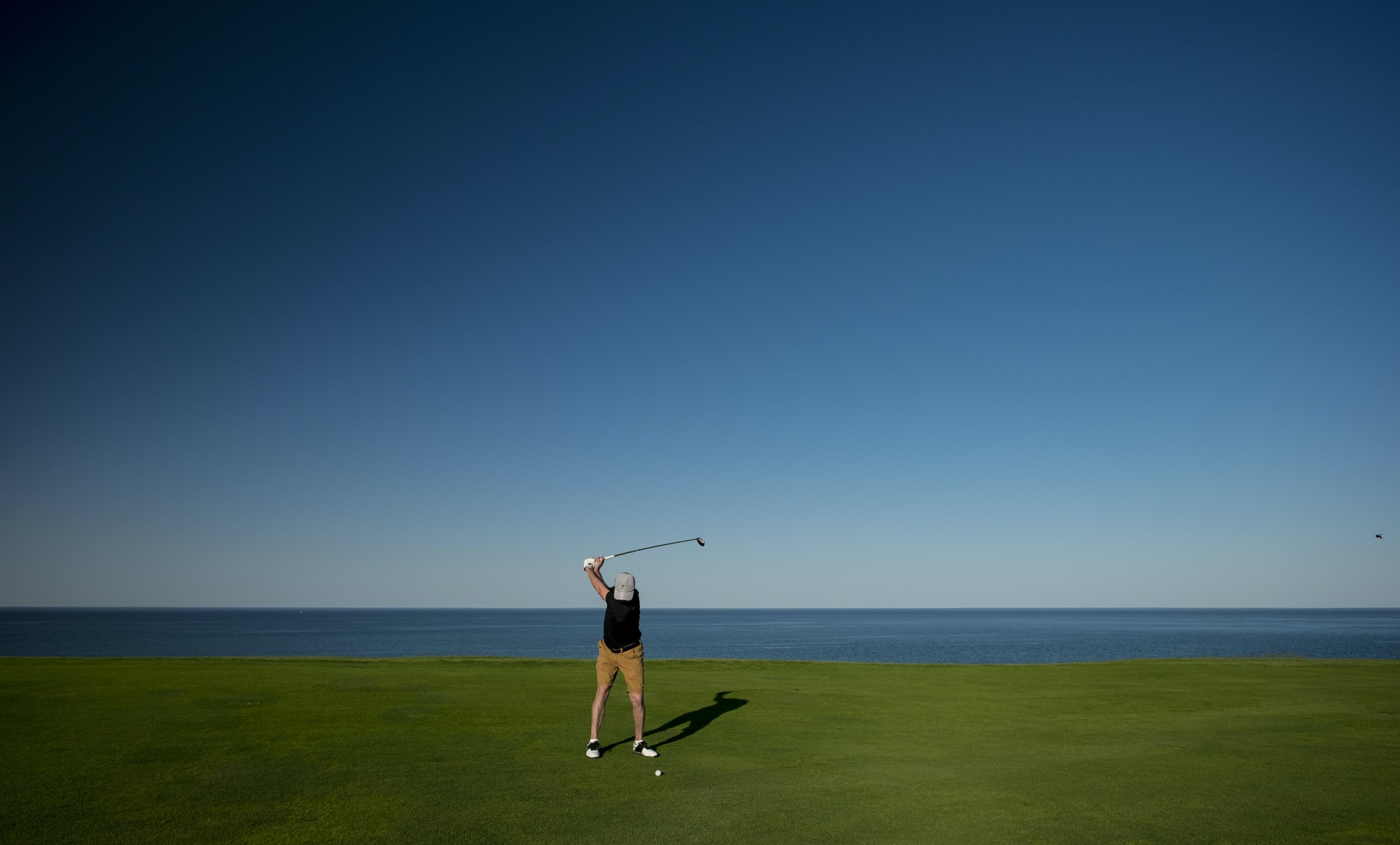 man standing on green grass field playing golf