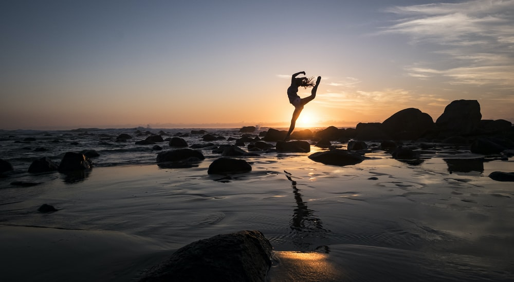 silhouette photography of woman standing on rock