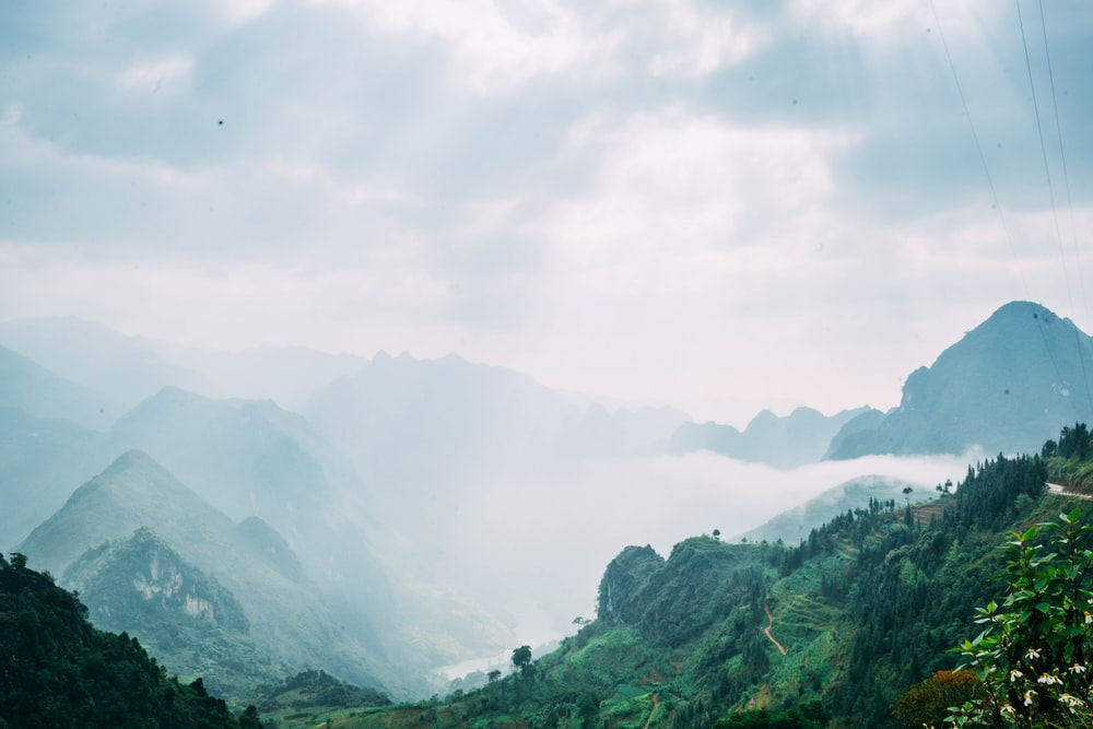photography of mountains with fog during daytime