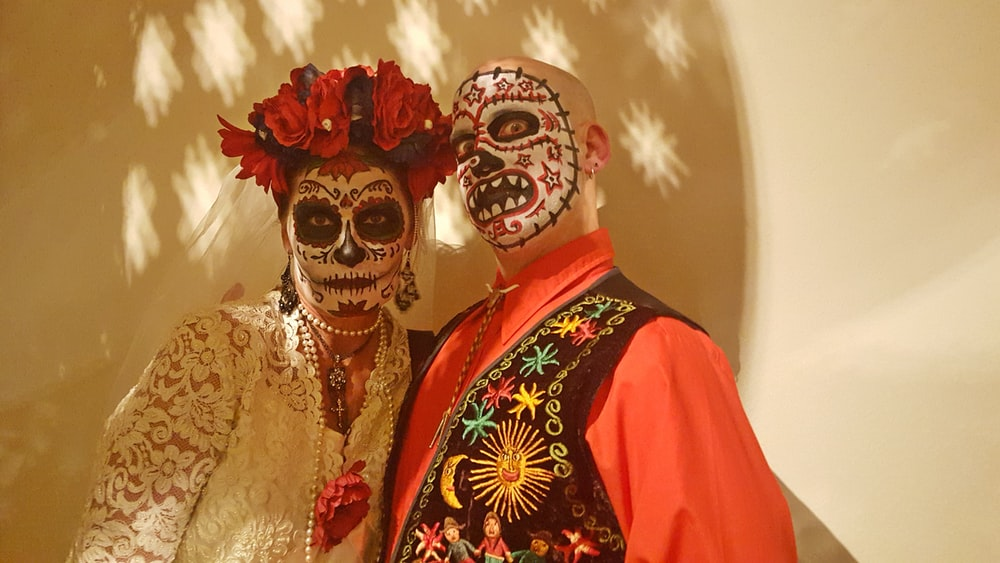 man and woman with face paint standing next to white wall