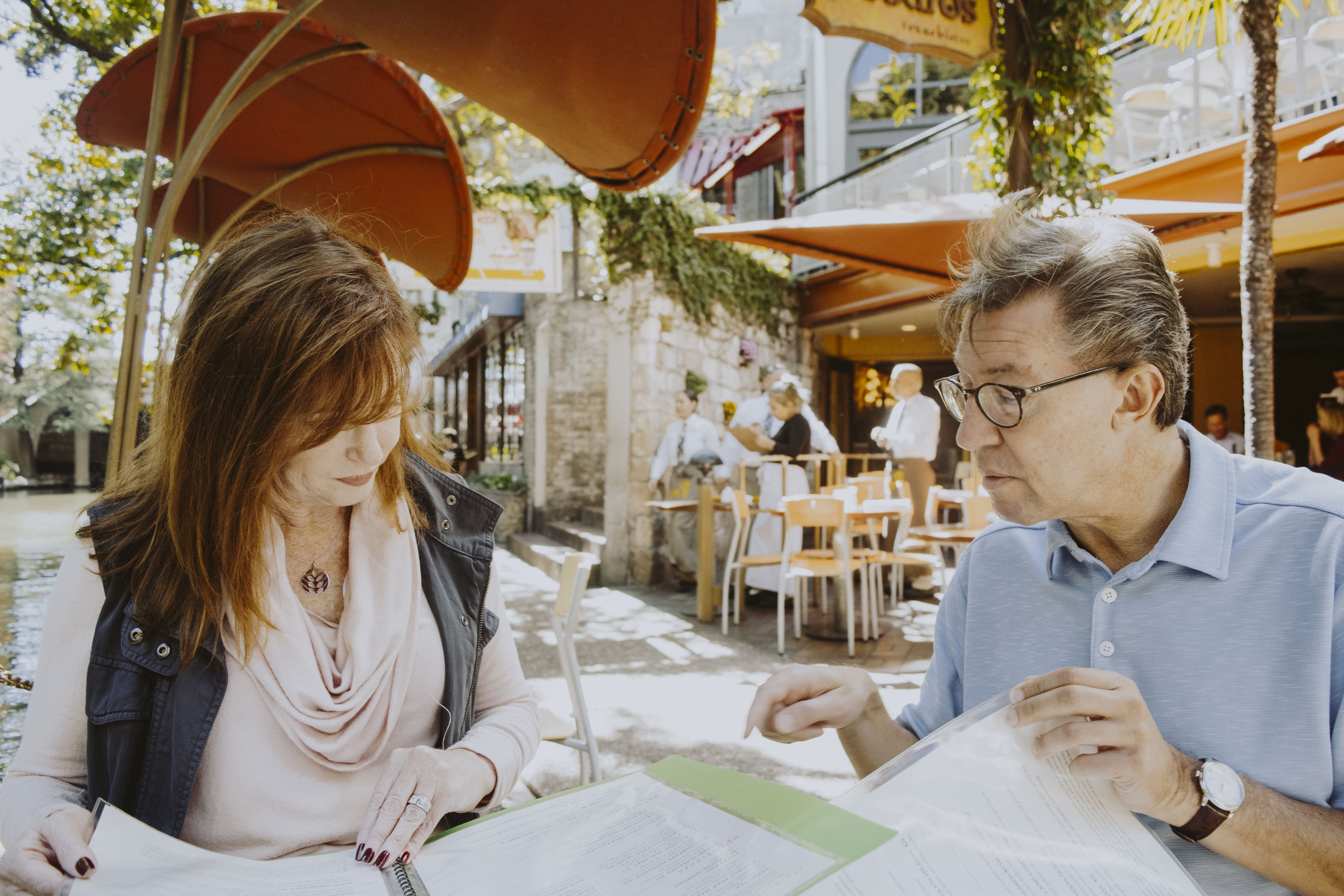 man and woman sitting down near table while reading outside cafe during daytime