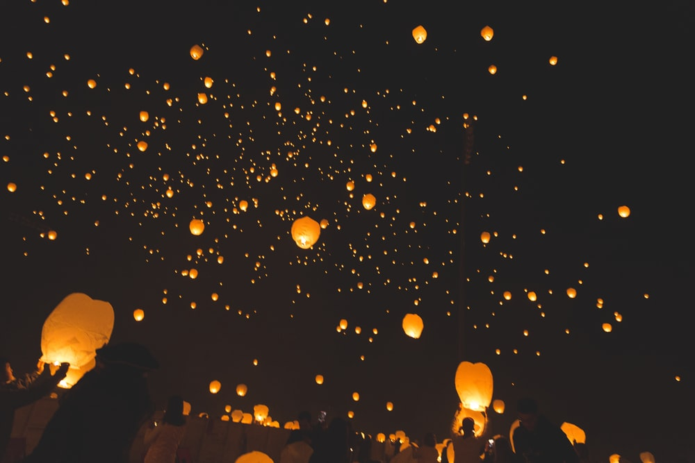 people raising sky lanterns